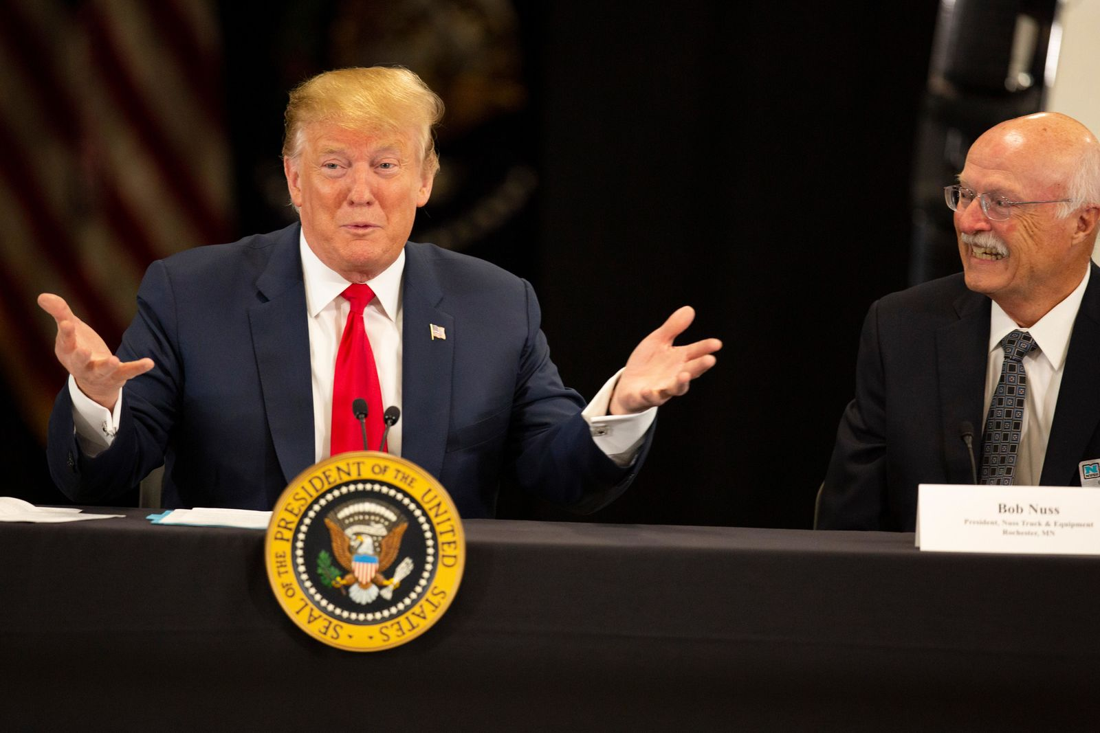 President Donald Trump talks as Bob Nuss of Nuss Truck and Equipment reacts Monday, April 15, 2019, in Burnsville, Minn. (AP Photo/Andy Clayton-King)