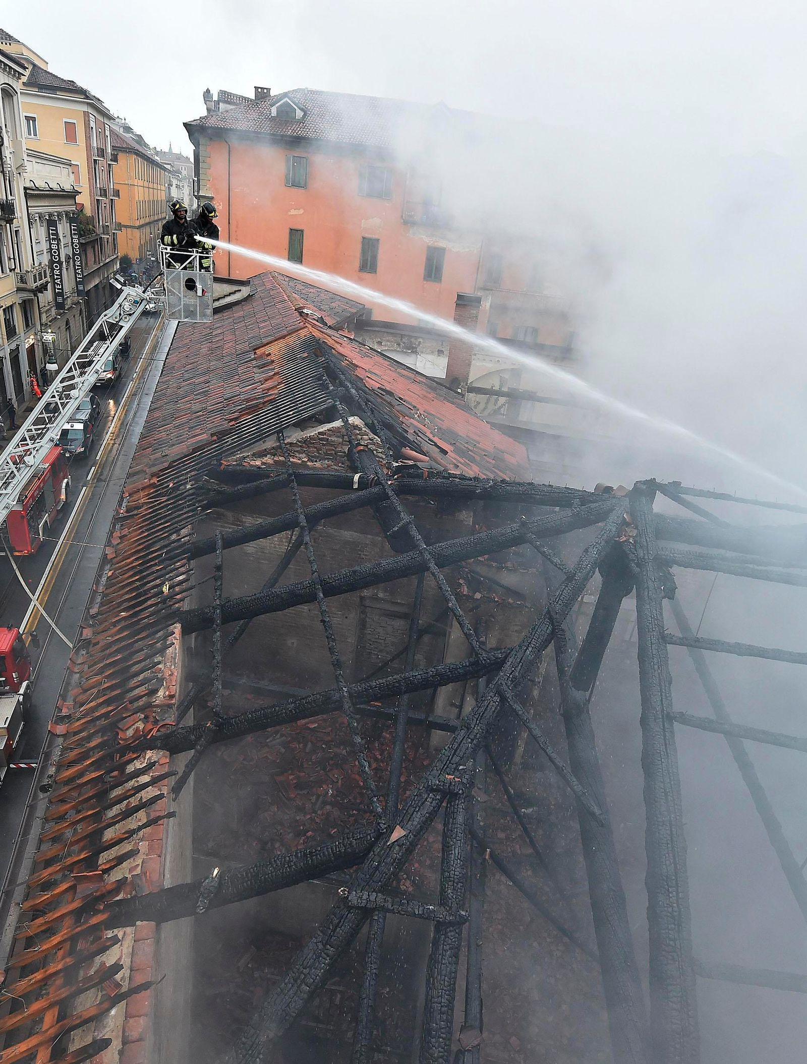 Firefighters put out a fire on the rooftop of the Cavallerizza Reale, in Turin, northern Italy, Monday, Oct. 21, 2019(Alessandro Di Marco/ANSA via AP)