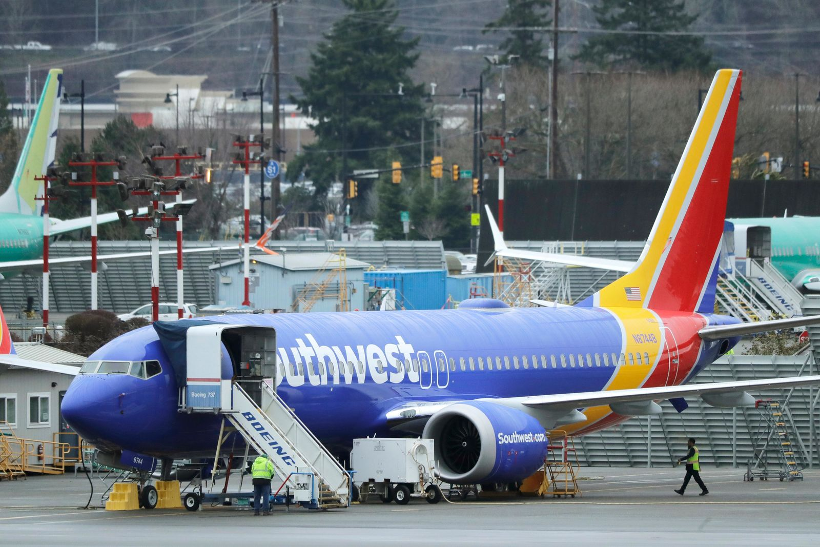 FILE - In this Dec. 11, 2019, file photo workers walk near a Southwest Airlines Boeing 737 Max airplane parked at Renton Municipal Airport in Renton, Wash. (AP Photo/Ted S. Warren, File)