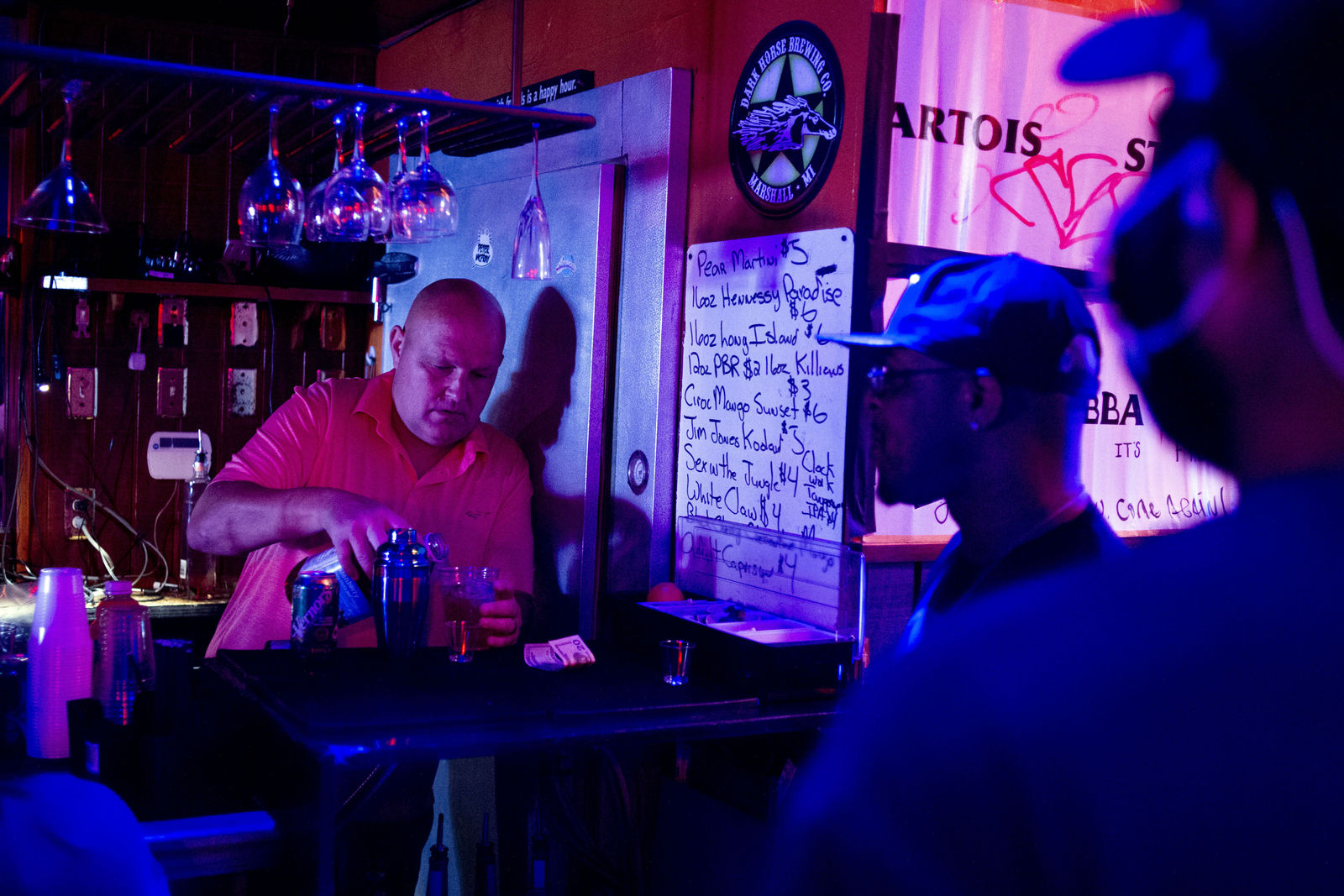 FILE - In this  June 8, 2020, file photo, Rodney Ott, owner of The Loft, makes mixed drinks from behind the bar for patrons as he reopens fully for the first time amid the coronavirus outbreak in downtown Flint, Mich. Authorities are closing honky tonks, bars and other drinking establishments in some parts of the U.S. to stem the surge of COVID-19 infections — a move backed by sound science about risk factors that go beyond wearing or not wearing masks. (Jake May/The Flint Journal via AP, File)
