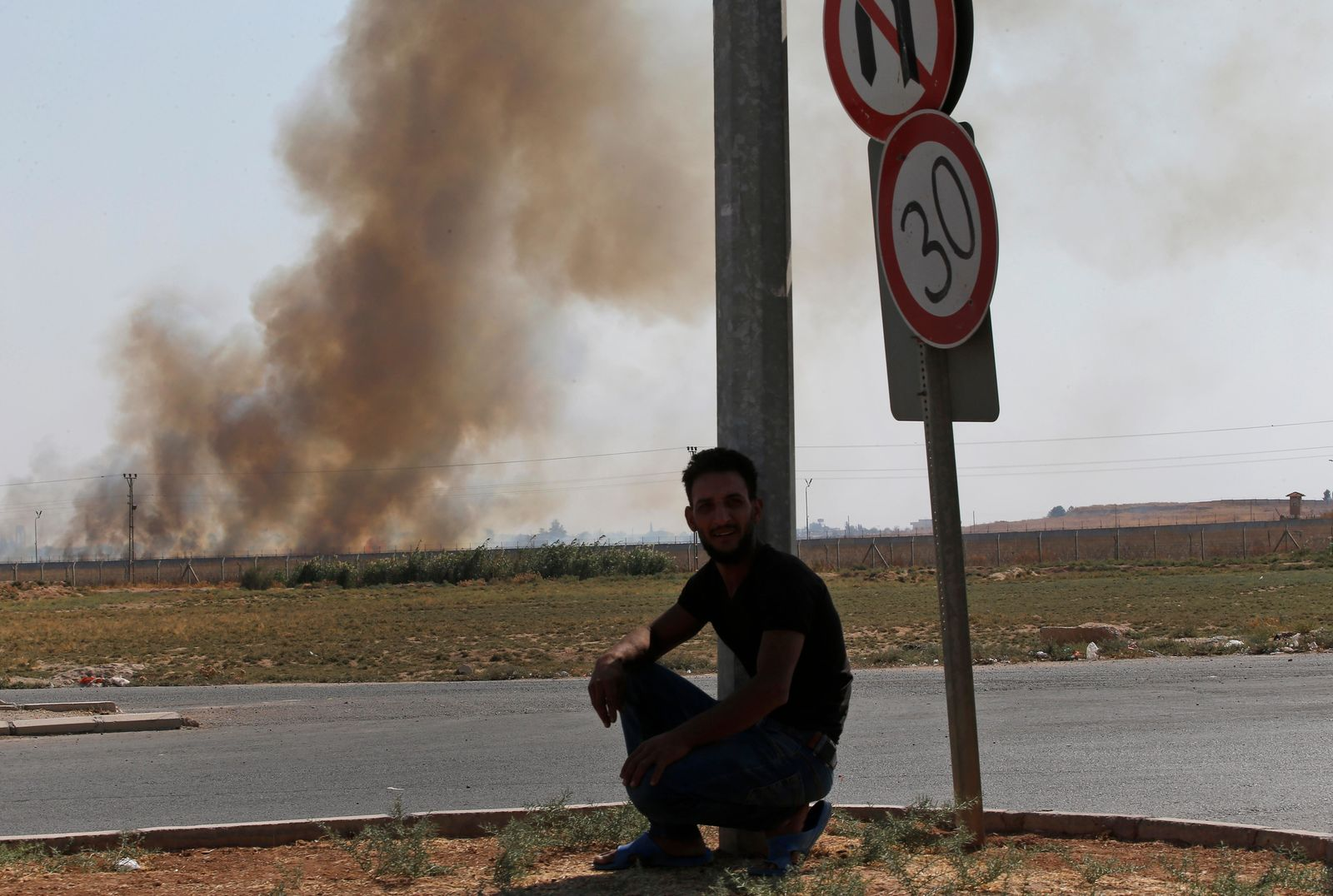 A man watches from Akcakale, Sanliurfa province, southeastern Turkey, as smoke billows from targets in Tel Abyad, Syria, during bombardment by Turkish forces, Sunday, Oct. 13, 2019. (AP Photo/Lefteris Pitarakis)