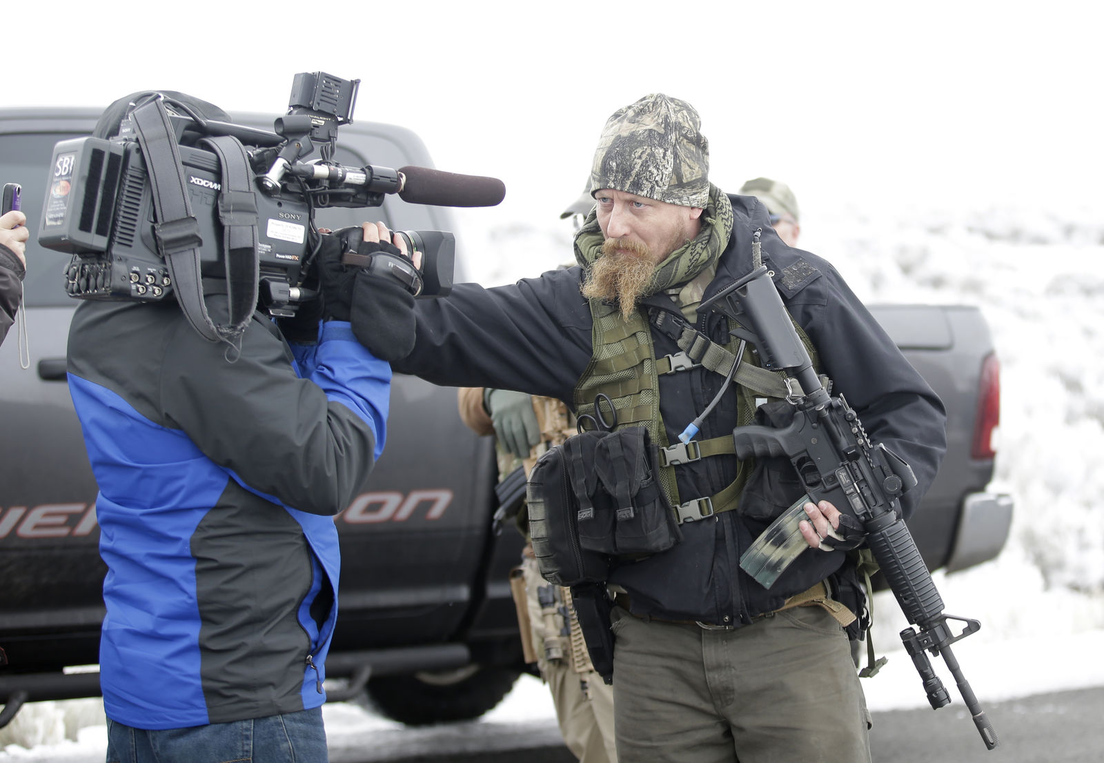 "A man standing guard pushes a videographer aside after members of the ""3% of Idaho"" group along with several other organizations arrived at the Malheur National Wildlife Refuge near Burns, Ore., on Saturday, Jan. 9, 2016. A small, armed group has been occupying the remote national wildlife refuge in Oregon for a week to protest federal land use policies. (AP Photo/Rick Bowmer)"