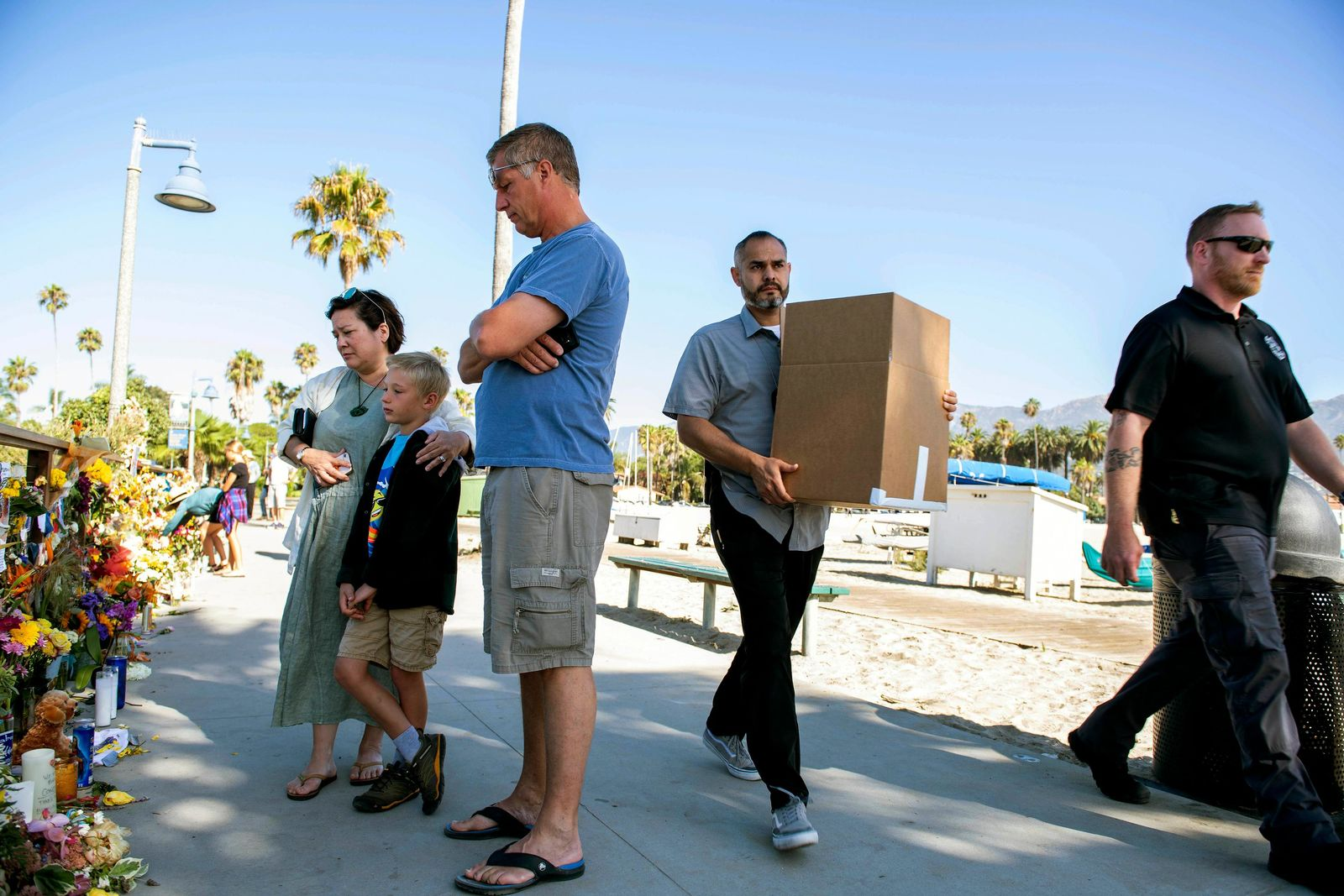 People gather around a memorial for the victims of the Conception dive boat fire, as authorities carry out boxes after a search at the Truth Aquatics' offices, the California company that owned the scuba diving boat that caught fire and killed dozens of people last week, on the Santa Barbara Harbor in Santa Barbara, Calif., Sunday, Sept. 8, 2019. . (AP Photo/ Christian Monterrosa)