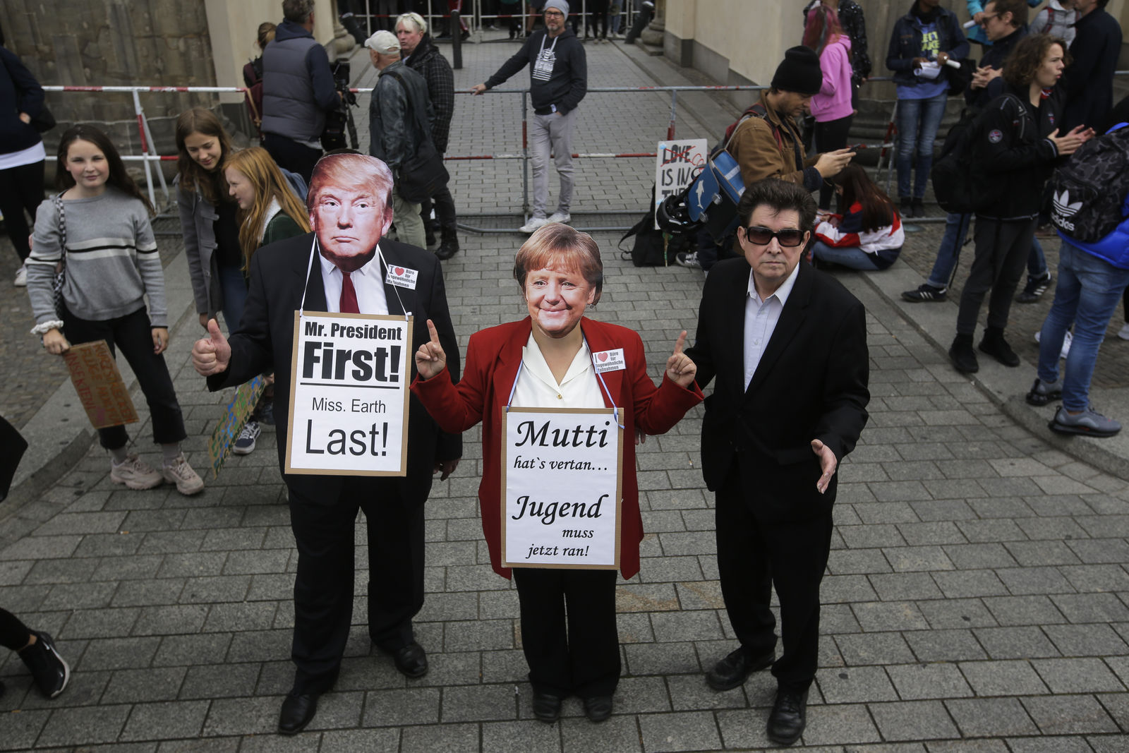 People wear masks of US President Donald Trump and German Chancellor Angela Merkel as they attend a 'Fridays For Future' rally at the Brandenburg Gate in Berlin, Germany, Friday, Sept. 20, 2019. rman slogan reads:  'Mom has missed it, youth has to do it now'. (AP Photo/Markus Schreiber)
