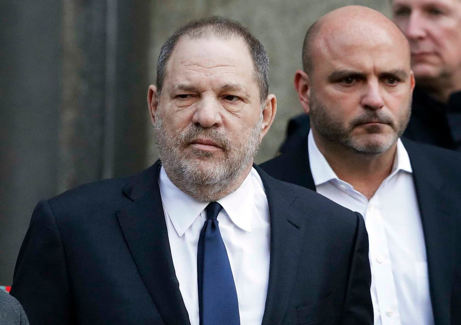FILE - In this Thursday, Dec. 20, 2018, file photo, Harvey Weinstein, center, leaves New York Supreme Court in New York. Weinstein's lawyers say a New York judge should reject sex trafficking claims in a class-action civil lawsuit against the movie mogul. (AP Photo/Mark Lennihan, File)