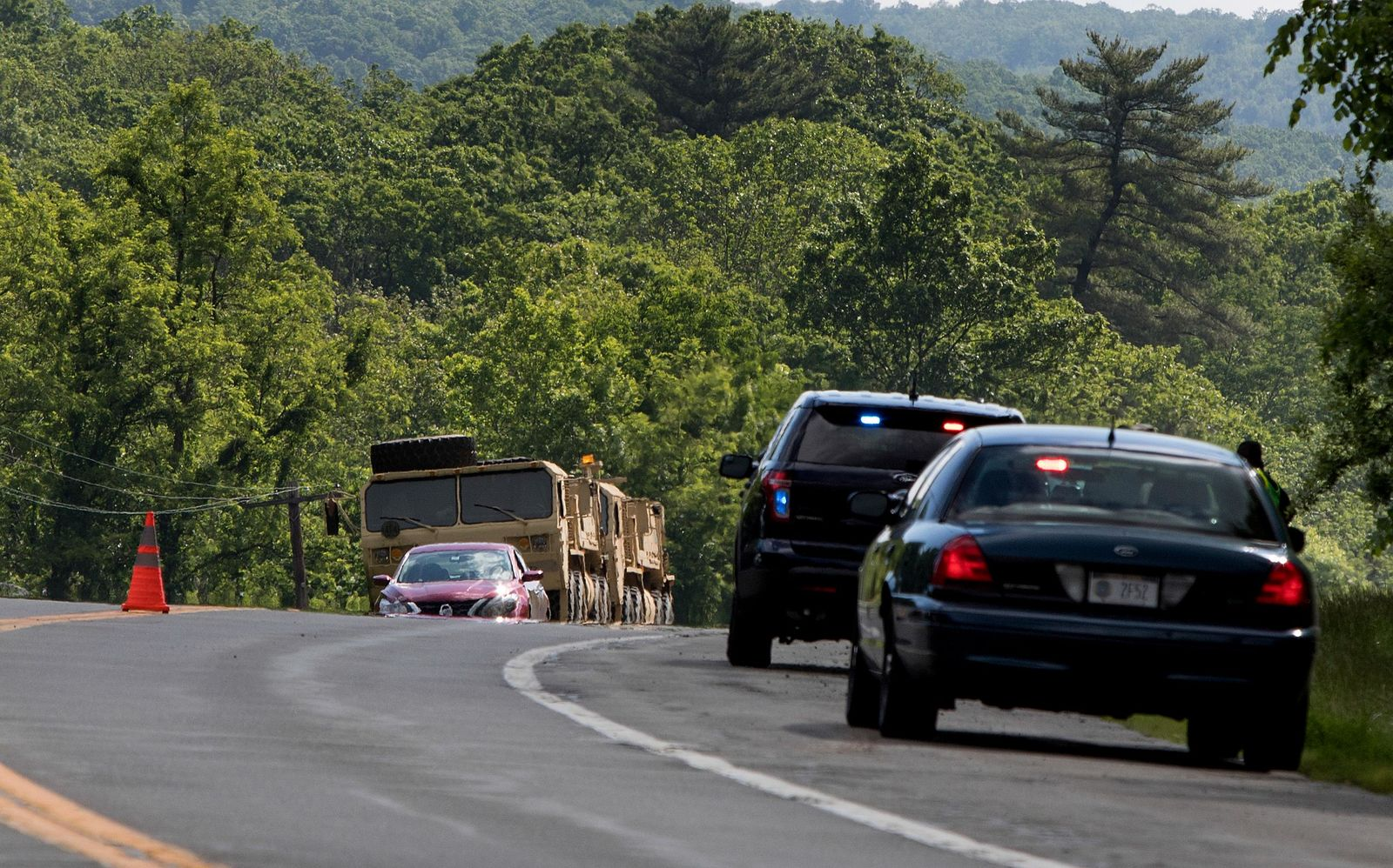 Military vehicles sit alongside Route 293 near the site where an armored personnel vehicle overturned killing at least one person, Thursday, June 6, 2019, in Cornwall, N.Y.{ } (AP Photo/Allyse Pulliam)