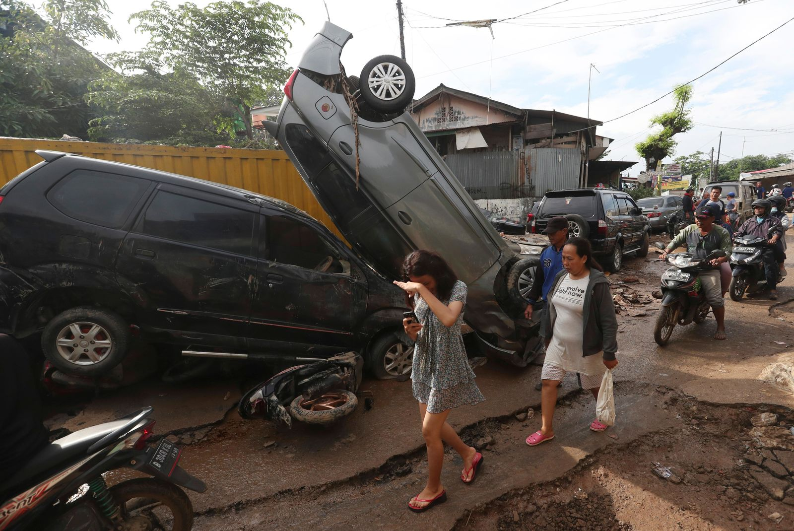Residents walk near the wreckage of cars that were swept away by flood in Bekasi, West Java, Indonesia, Friday, Jan. 3, 2020.Severe flooding in greater Jakarta has killed scores of people and displaced tens of thousands others, the country's disaster management agency said. (AP Photo/Achmad Ibrahim)