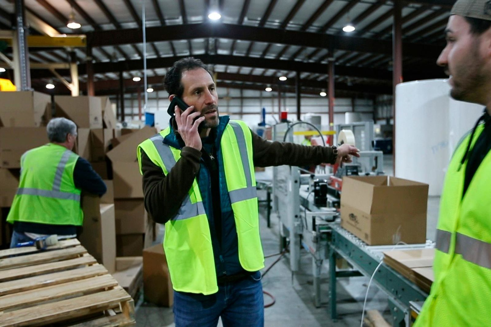 Marc Cooper takes a call while directing workers packing toilet paper at the Tissue Plus factory, Wednesday, March 18, 2020, in Bangor, Maine. The new company has been unexpectedly busy because of the shortage of toilet paper brought on by hoarders concerned about the coronavirus. (AP Photo/Robert F. Bukaty)