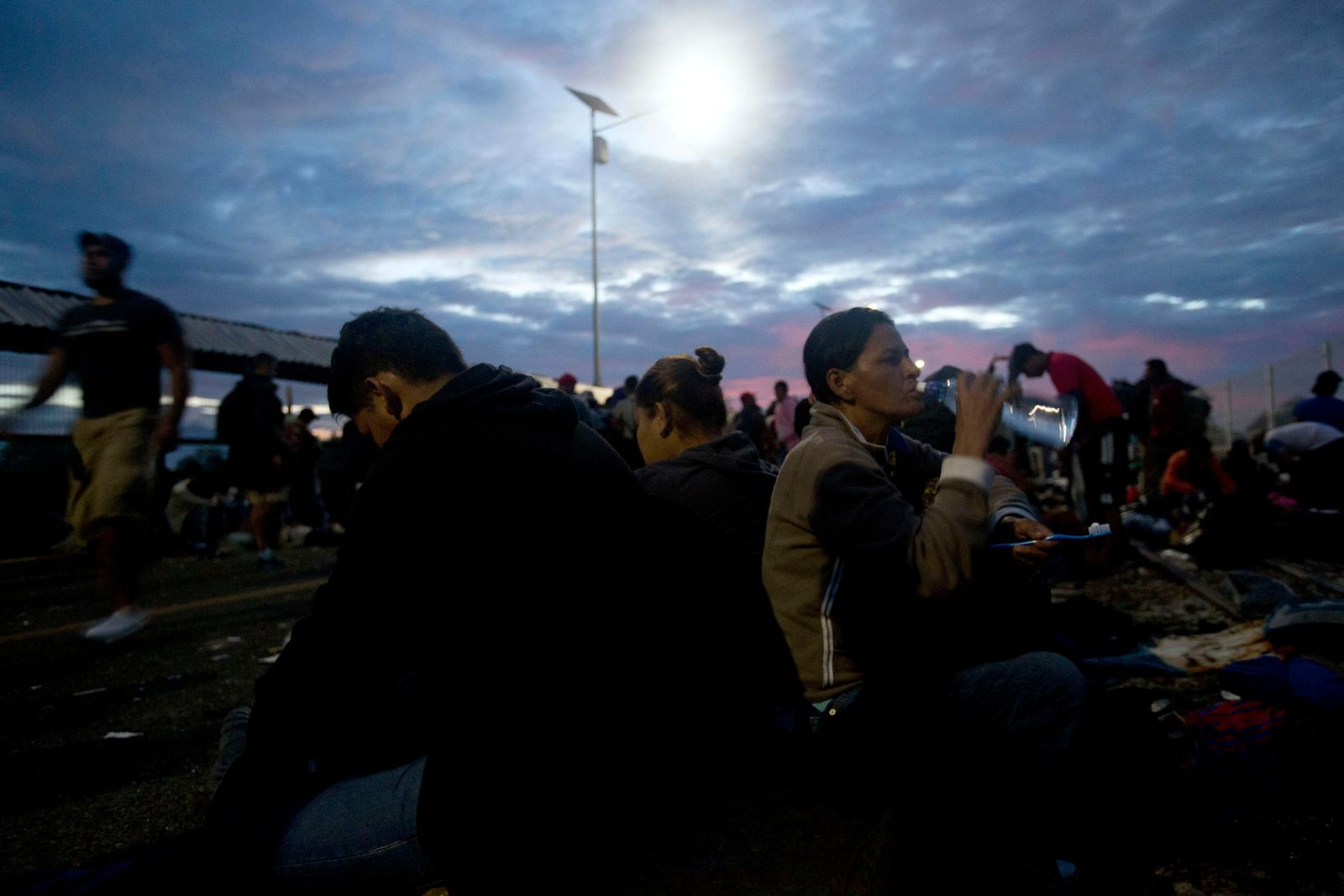 Migrants bound for the U.S.-Mexico border wait on a bridge that stretches over the Suchiate River, connecting Guatemala and Mexico, in Tecun Uman, Guatemala, early Saturday, Oct. 20, 2018. (AP Photo/Moises Castillo)