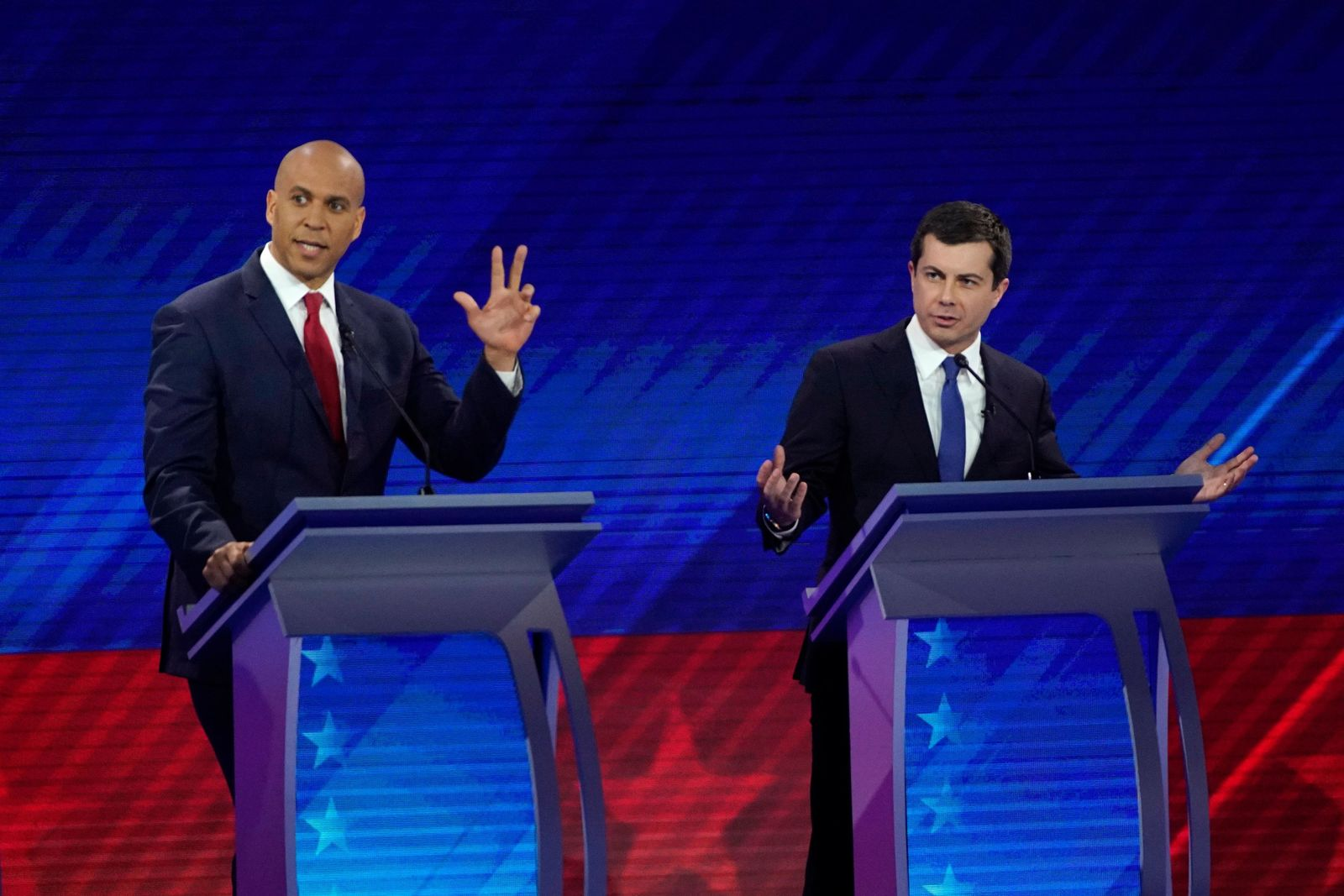 Sen. Cory Booker, D-N.J., left, and South Bend Mayor Pete Buttigieg, right, try to respond to a question Thursday, Sept. 12, 2019, during a Democratic presidential primary debate hosted by ABC at Texas Southern University in Houston. (AP Photo/David J. Phillip)