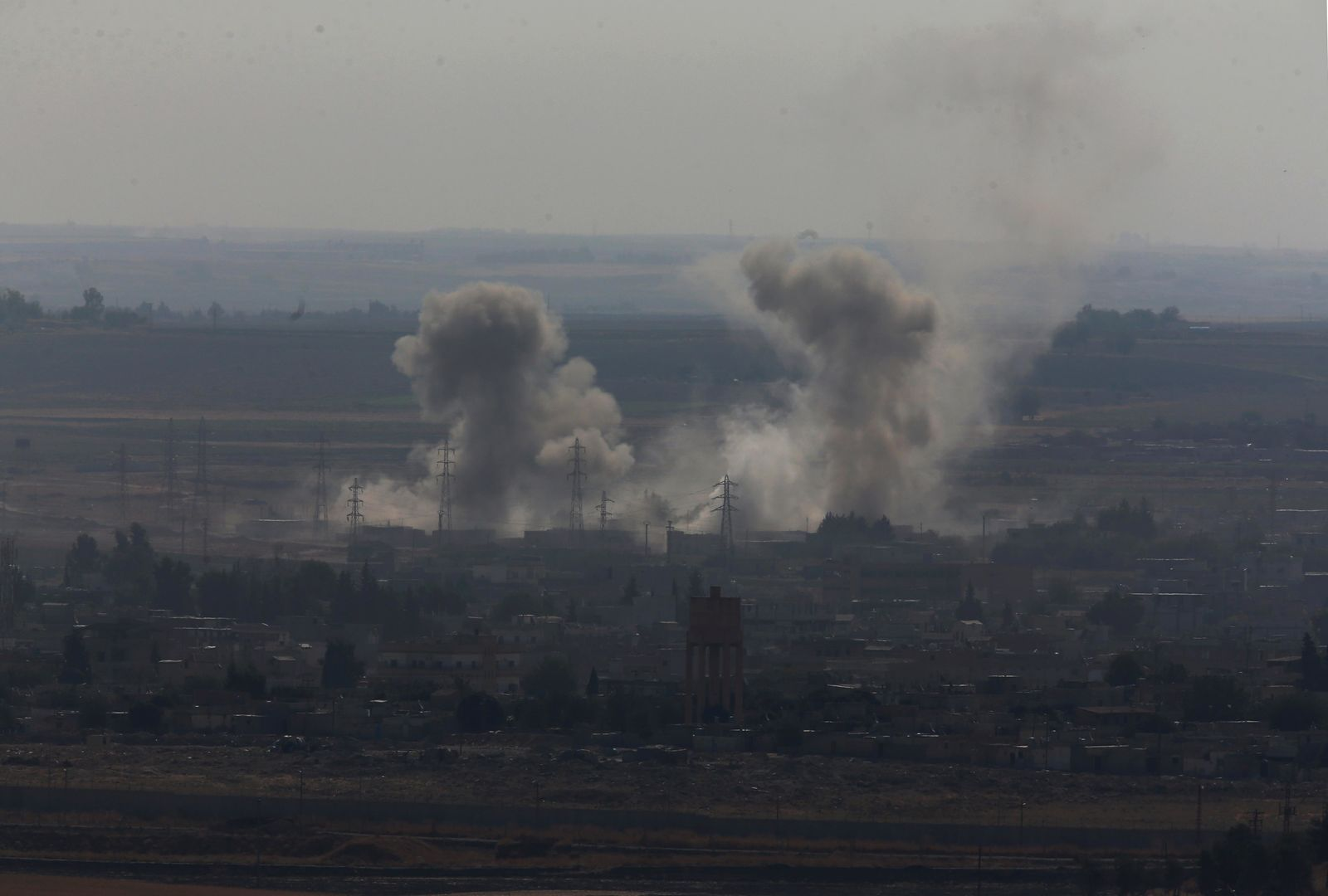 In this photo taken from the Turkish side of the border between Turkey and Syria, in Ceylanpinar, Sanliurfa province, southeastern Turkey, smoke billows from targets in Ras al-Ayn, Syria, caused by bombardment by Turkish forces, Tuesday, Oct. 15, 2019.{ } (AP Photo/Lefteris Pitarakis)