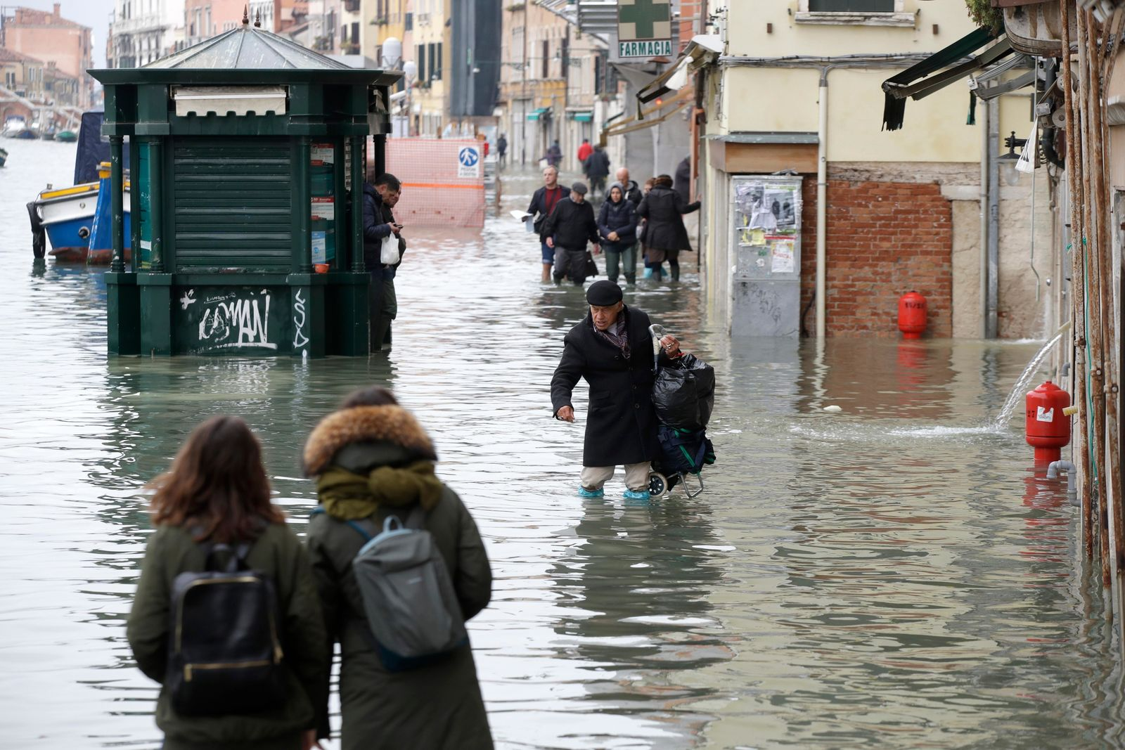 People wade through water during a high tide, in Venice, Wednesday, Nov. 13, 2019. The high-water mark hit 187 centimeters (74 inches) late Tuesday, Nov. 12, 2019, meaning more than 85% of the city was flooded. The highest level ever recorded was 194 centimeters (76 inches) during infamous flooding in 1966. (AP Photo/Luca Bruno)