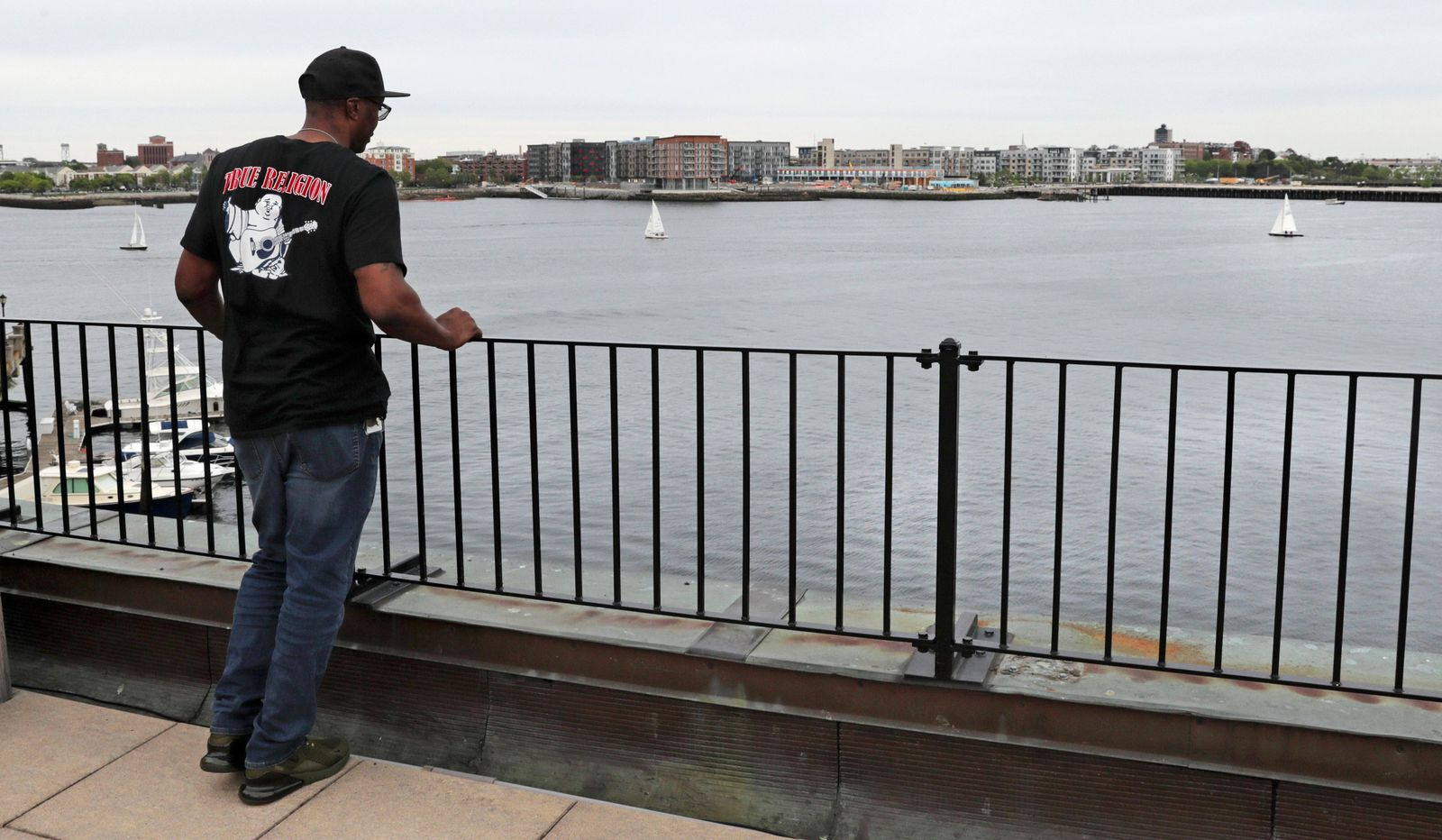 In this Tuesday June 4, 2019 photograph, Sean Ellis watches boats sailing on Boston Harbor from the roof deck of his attorney Rosemary Scapicchio's office after an afternoon indoor meeting in Boston.{ } (AP Photo/Charles Krupa)