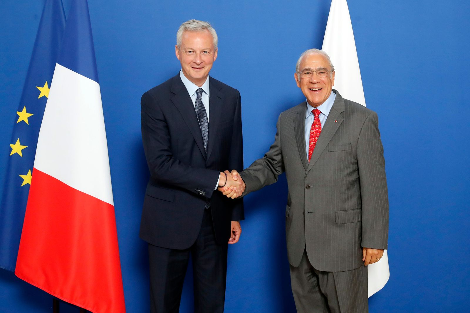 French Finance Minister Bruno Le Maire, left, meets with OECD chief Angel Gurria to plan for international taxes on digital giants like Amazon and Google at Bercy Economy ministry in Paris, Thursday, Aug. 29, 2019. France recently introduced a 3% tax on the companies' French revenues, prompting U.S. President Donald Trump to threaten tariffs on French wine in response.(AP Photo/Francois Mori)