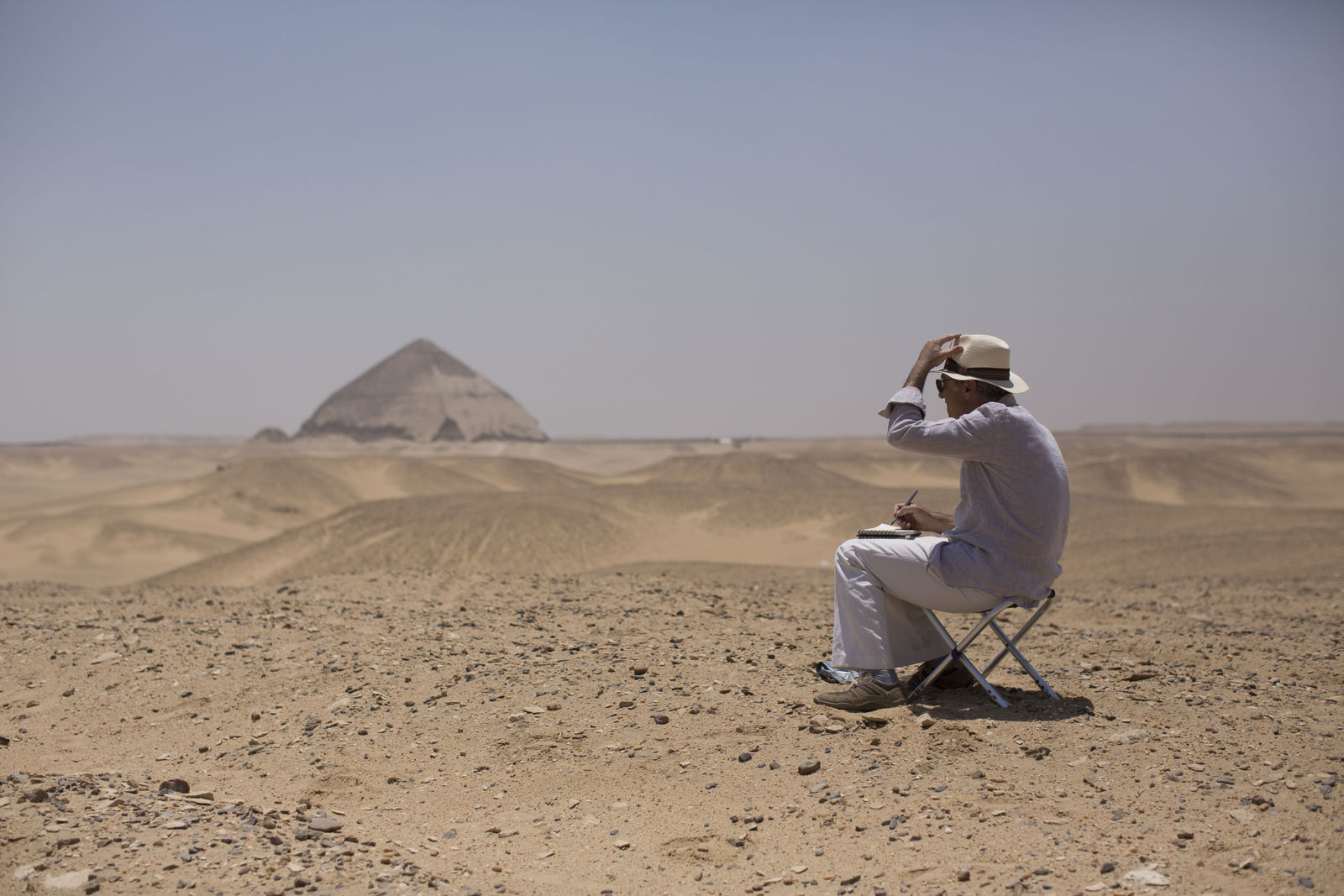 A member of an international delegation sketches the site of the Bent Pyramid during an event opening the pyramid and its satellites for visitors in Dashur, Egypt, Saturday, July 13, 2019. (AP Photo/Maya Alleruzzo)