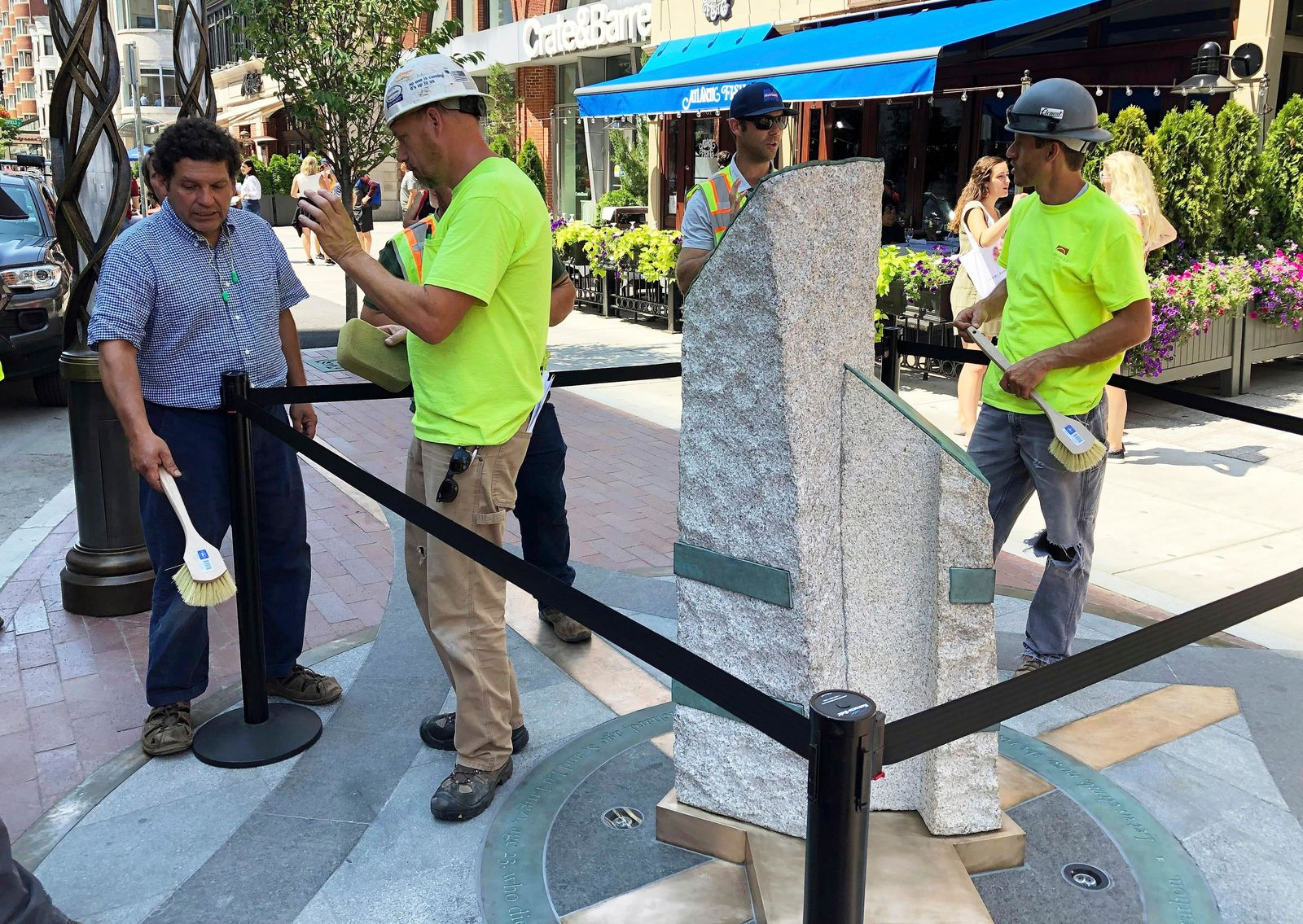 Sculptor Pablo Eduardo, left, and workers make final touches to stone pillars stand along Boylston Street after installation was finished, Monday, Aug. 19, 2019, in Boston to memorialize the Boston Marathon bombing victims at the sites where they were killed. (AP Photo/Philip Marcelo)