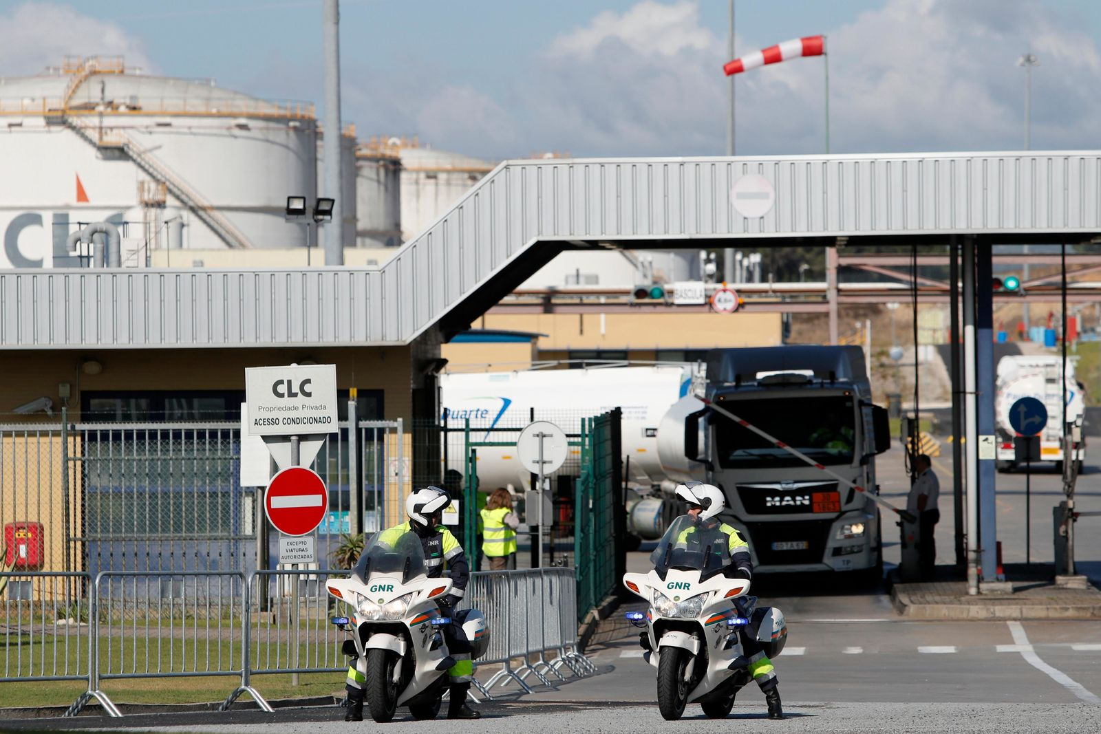 Police officers wait to escort a convoy of fuel trucks leaving a fuel depot in Aveiras, outside Lisbon, Monday, Aug. 12, 2019.{ } (AP Photo/Armando Franca)