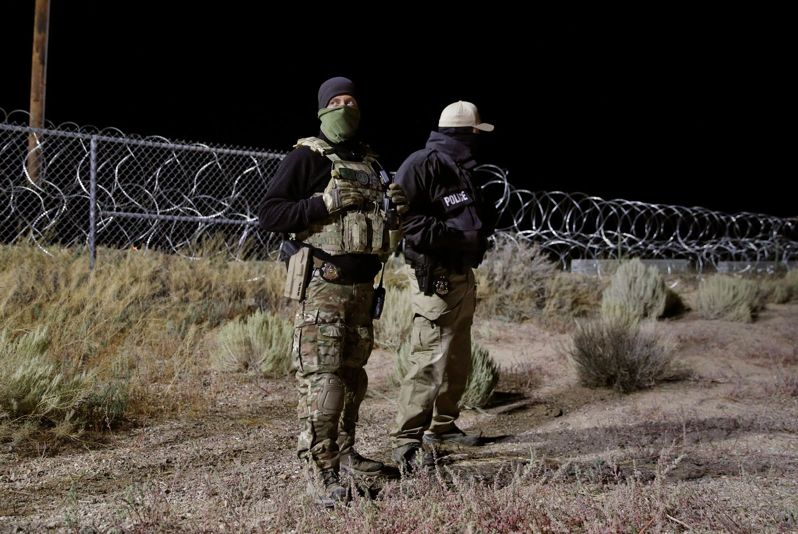 "Police officers guard an entrance to the Nevada Test and Training Range near Area 51 Friday, Sept. 20, 2019, near Rachel, Nev. People gathered at the gate inspired by the ""Storm Area 51"" internet hoax. (AP Photo/John Locher)"