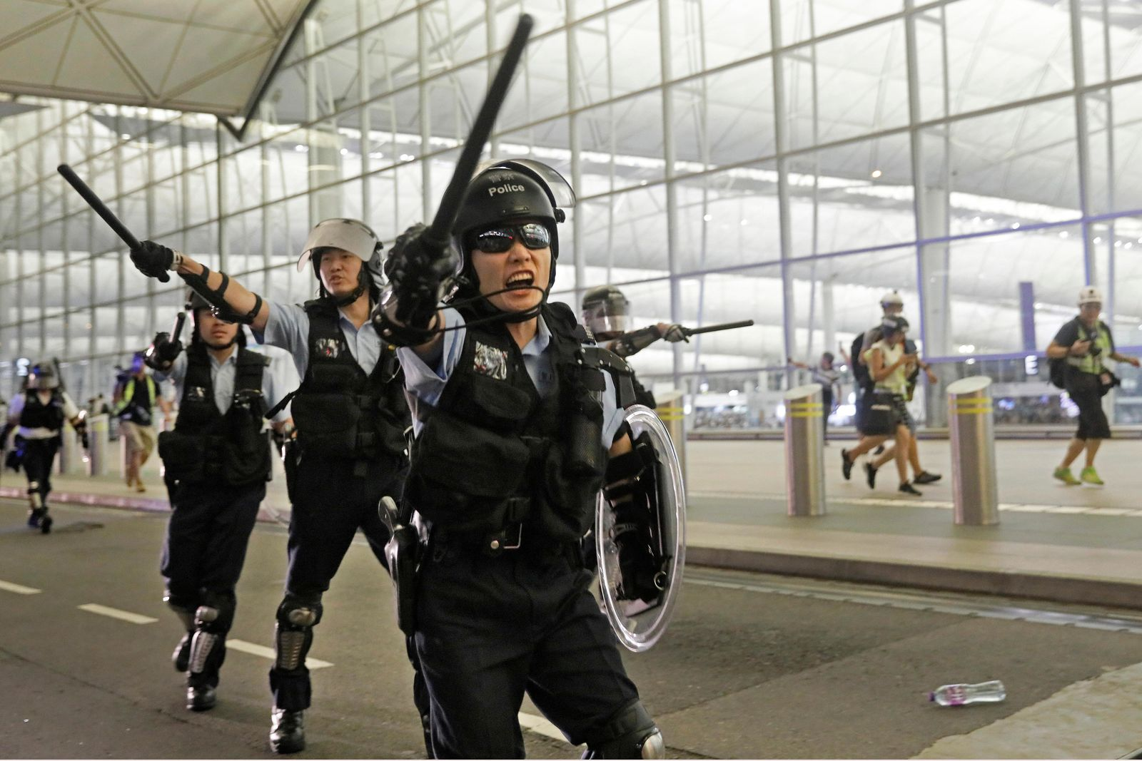 Policemen with batons and shields shout at protesters during a demonstration at the Airport in Hong Kong, Tuesday, Aug. 13, 2019. Riot police clashed with pro-democracy protesters at Hong Kong's airport late Tuesday night, a chaotic end to a second day of demonstrations that caused mass flight cancellations at the Chinese city's busy transport hub. (AP Photo/Vincent Yu)