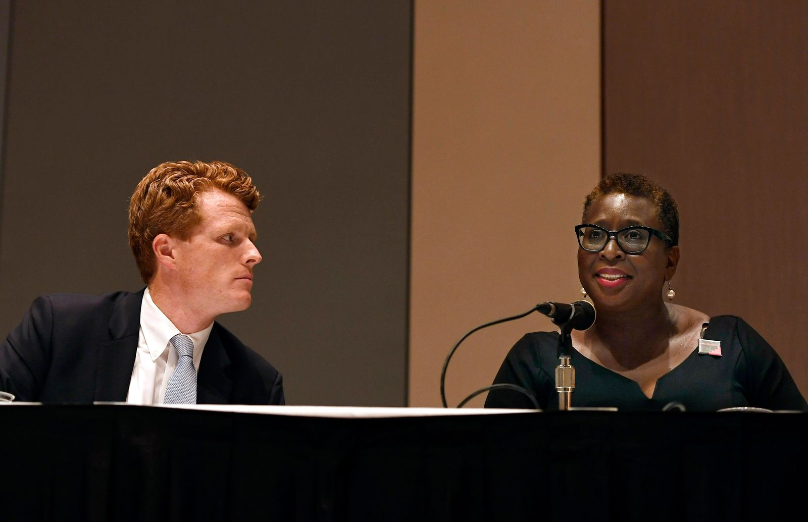 U.S. Rep. Joe Kennedy III, left, listens as Framingham Mayor Yvonne Spicer, right, speaks on a panel on race and politics, Saturday, Sept. 14, 2019, in Springfield, Mass. (AP Photo/Jessica Hill)