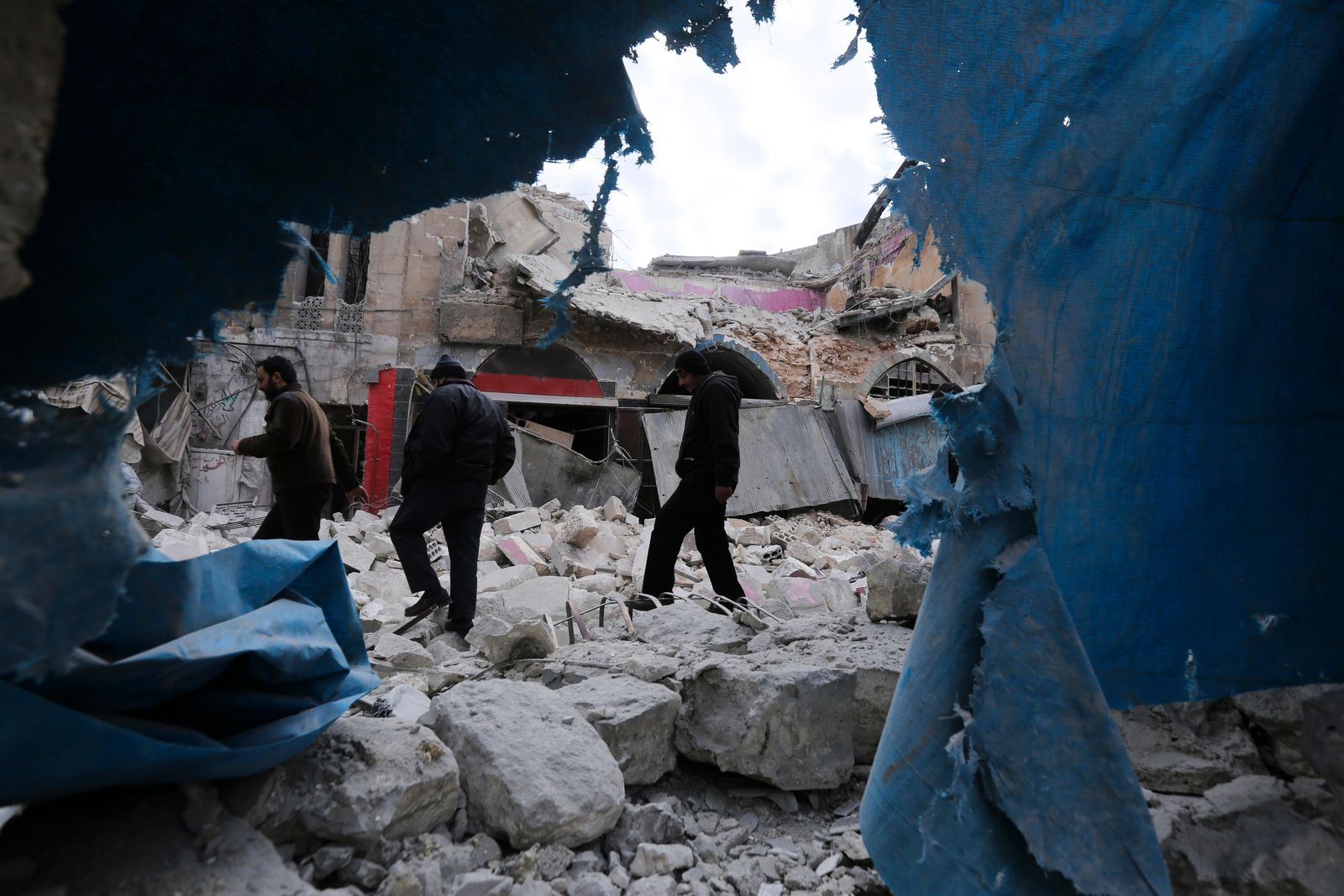 People walk past destruction by the government airstrikes in the town of Ariha, in Idlib province, Syria, Wednesday, Jan. 15, 2020. (AP Photo/Ghaith Alsayed)