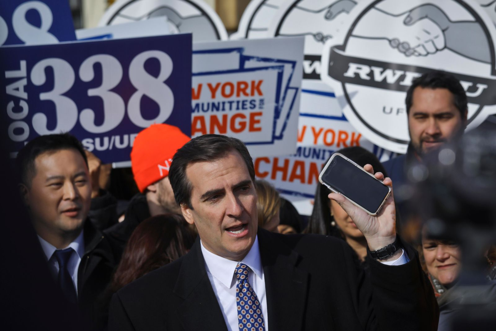 FILE - In this Nov. 14, 2018 file photo, New York State Sen. Michael Gianaris, center, calls on supporters to remove the Amazon app from their phones and boycott the company, as he address a coalition rally and press conference in New York. The first clue that opposition to the project could succeed in derailing the deal came in early February, when Gianaris was appointed to a seat on a state panel that often has to approve state funding for big economic development projects. According to the rules governing the 5-member Public Authorities Control Board, funds for any individual project can be vetoed by a single member, meaning that if the Amazon deal went before the board, Gianaris could kill it unilaterally. (AP Photo/Bebeto Matthews, File)