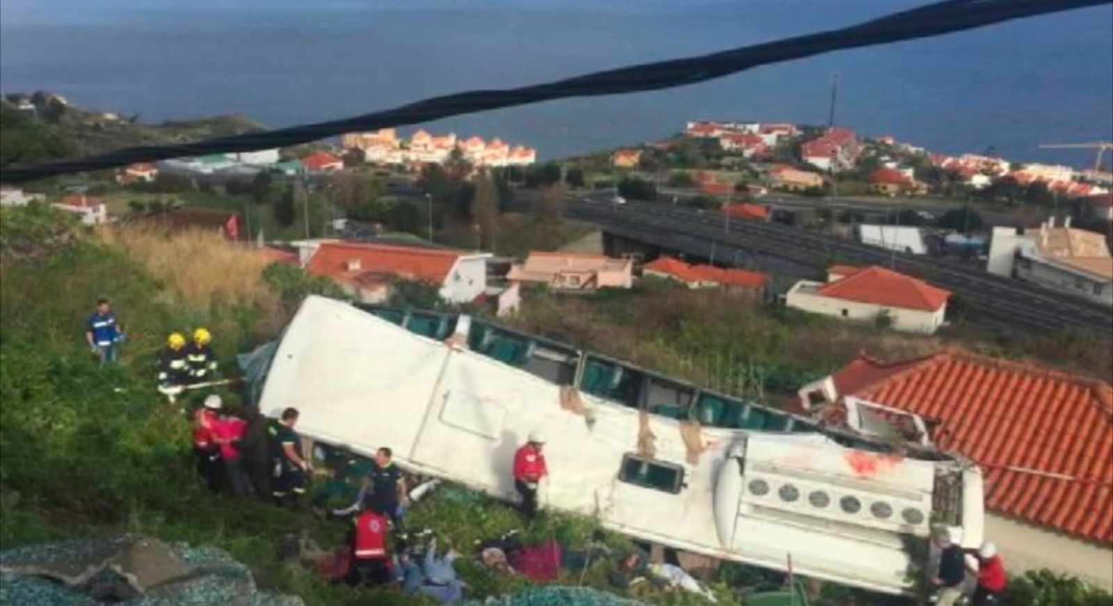 In this image from video, emergency services attend the scene after a tour bus crashed at Canico, on Portugal's Madeira Island, Wednesday April 17, 2019. (TVI via AP)