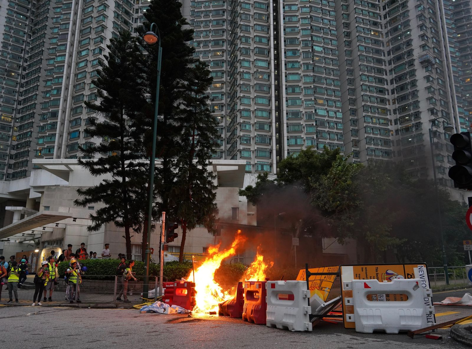 Firemen try to douse fire after protesters set fire to barricades and vandalized signages at Tung Chung near airport in Hong Kong, Sunday, Sept.1, 2019. (AP Photo/Vincent Yu)