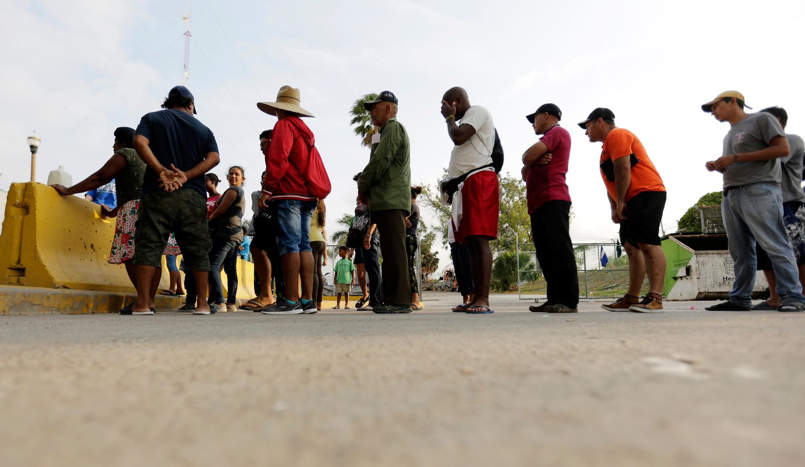 FILE - In this April 30, 2019, file photo, migrants seeking asylum in the United States line up for a meal provided by volunteers near the international bridge in Matamoros, Mexico. (AP Photo/Eric Gay, File)
