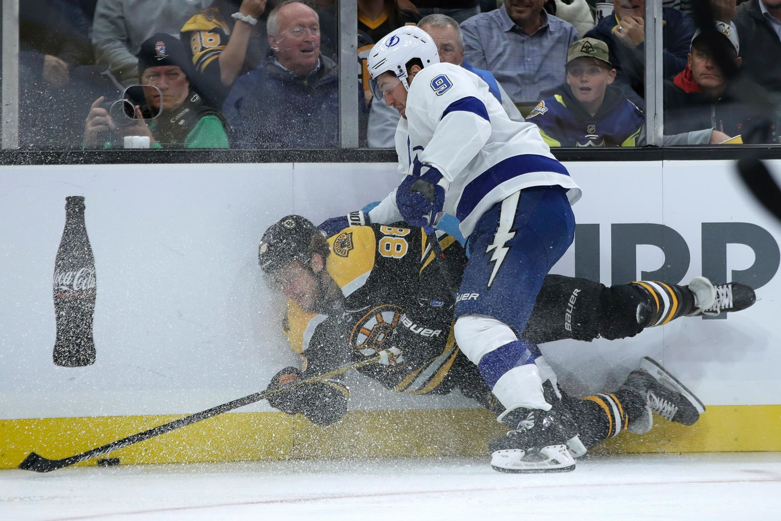 Boston Bruins right wing David Pastrnak (88) competes for the puck with Tampa Bay Lightning center Tyler Johnson (9) along the boards during the first period of an NHL hockey game Thursday, Oct. 17, 2019, in Boston. (AP Photo/Elise Amendola)