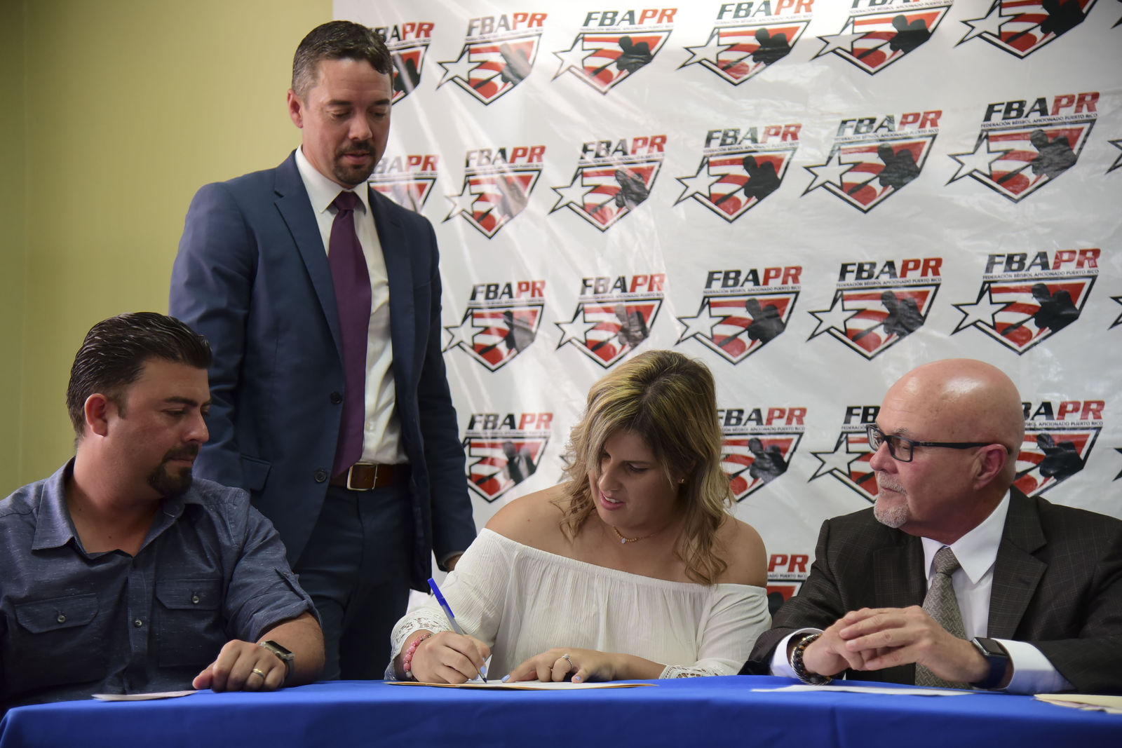 First baseman and member of the National Women's Baseball Team, Diamilette Quiles Alicea, center, signs with The Utuado Highlanders, one of the teams that participate in the Superior Double A Baseball League, in San Juan, Puerto Rico, Thursday, May 16, 2019.  Quiles Alicea signs the contract accompanied by Utuado mayor Ernesto Irizarry Salva, left, the representative of the Montaneses of Utuado Rafael Juarbe, second left, and the president of the Federation, Dr. Jose Quiles Rosas. (AP Photo/Carlos Giusti)