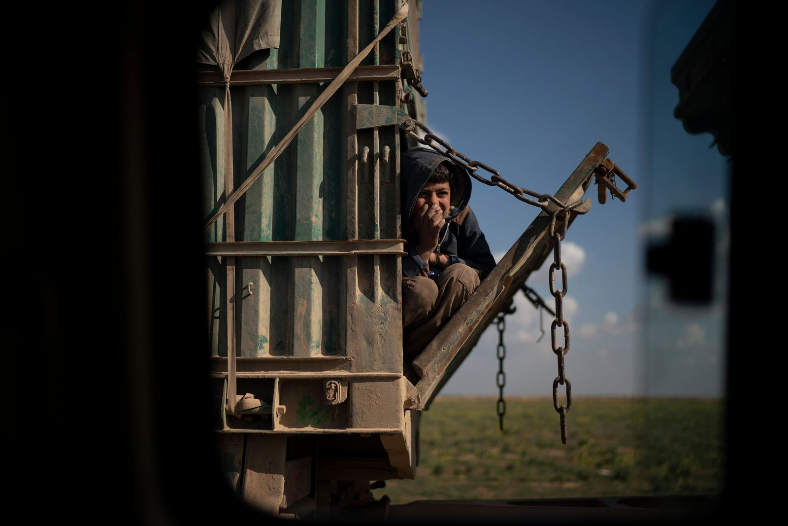 A boy rides in the back of a truck that is part of a convoy evacuating hundreds out of the last territory held by Islamic State militants, in Baghouz, eastern Syria, Wednesday, Feb. 20, 2019. The evacuation signals the end of a week long standoff and opens the way to U.S.-backed Syrian Democratic Forces (SDF) recapture the territory. (AP Photo/Felipe Dana)