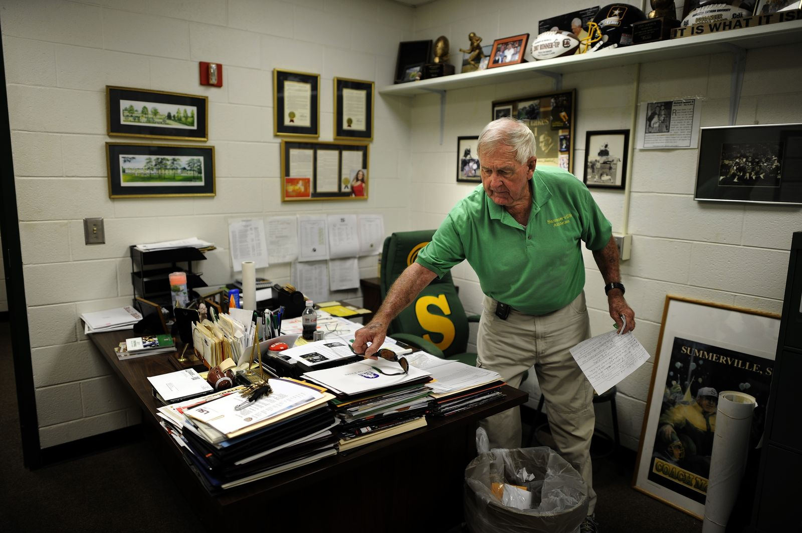FILE - In this Oct. 24, 2012, file photo, Summerville High School coach John McKissick prepares to leave his office for the school's practice field in Summerville, S.C. McKissick, whose 621 victories at South Carolina's Summerville High made him the nation's winningest football coach at any level, has died at age 93. Dorchester County Coroner Paul Brouthers said McKissick had been in hospice care and died Thursday, Nov. 28, 2019, surrounded by family. (AP Photo/Stephen Morton, File)