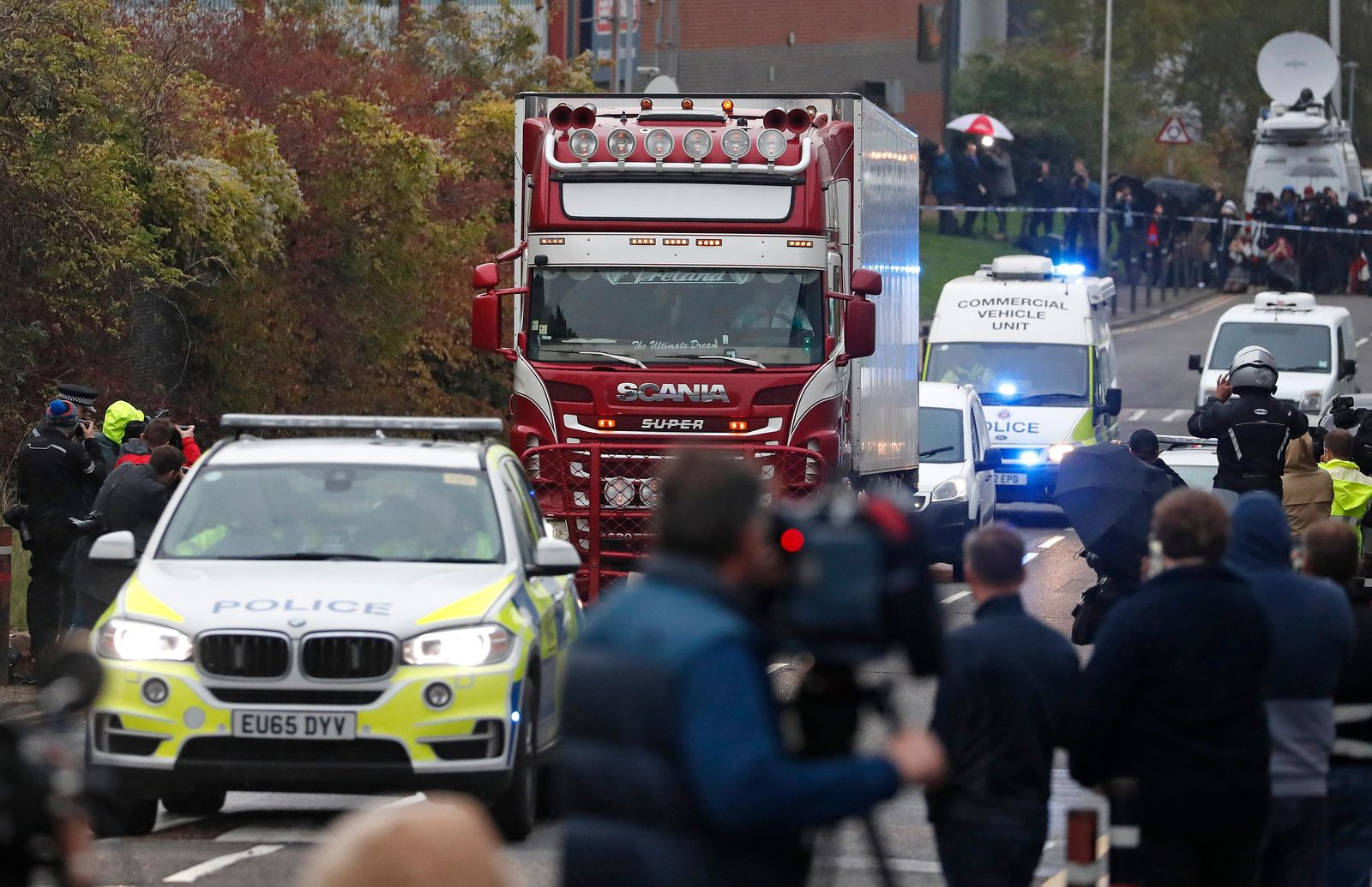 Police escort the truck, that was found to contain a large number of dead bodies, as they move it from an industrial estate in Thurrock, south England, Wednesday Oct. 23, 2019.(AP Photo/Alastair Grant)