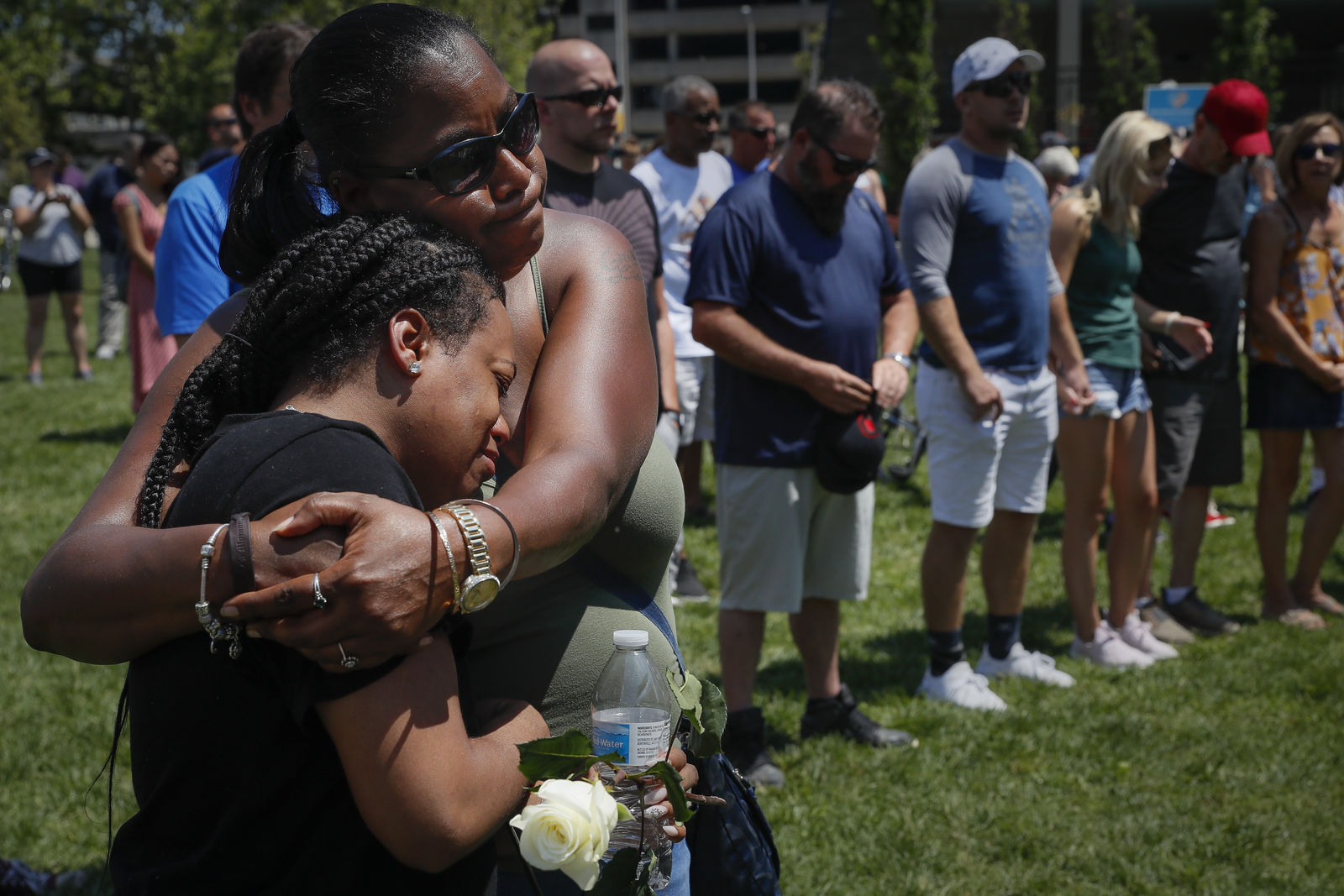 FILE - In this Aug. 4, 2019, file photo, mourners gather at a vigil following a nearby mass shooting in Dayton, Ohio. In the days and weeks since three high-profile shootings took the lives of more than two dozen people in just a week's time, law enforcement authorities have reported seeing a spike in the number of tips they are receiving from concerned relatives, friends and co-workers of people who appear bent on carrying out the next mass shooting. (AP Photo/John Minchillo, FIle)
