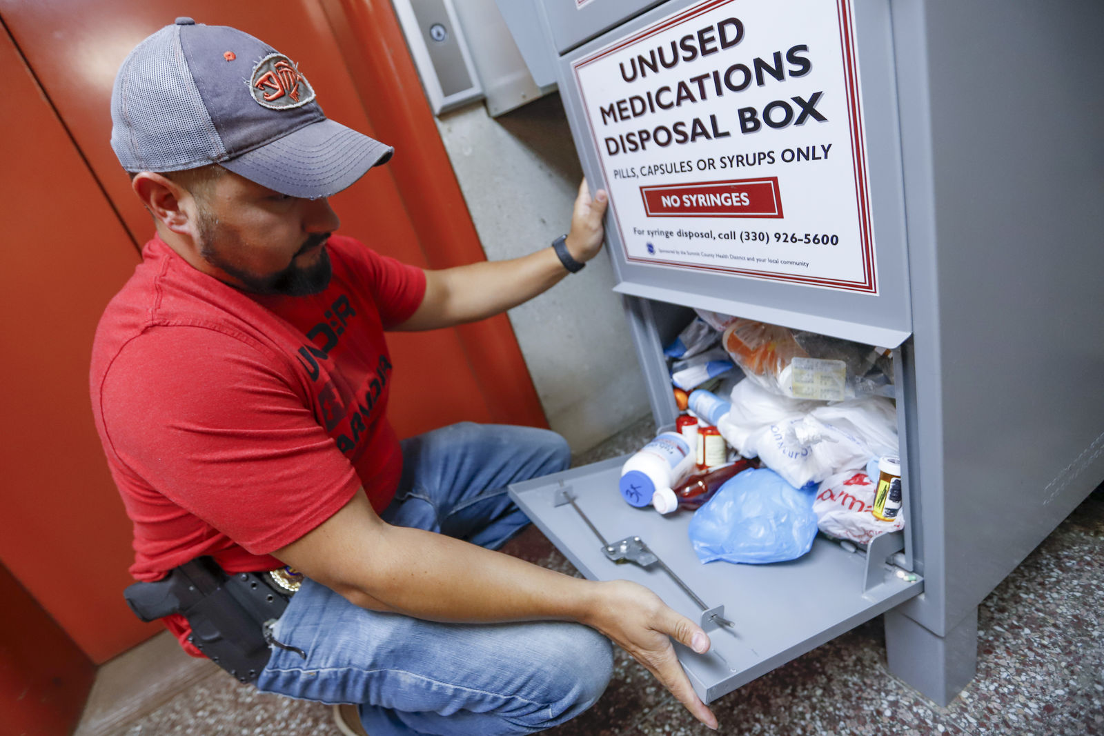 FILE - In this Sept. 11, 2019, photo, narcotics detective Paul Laurella retrieves unused medications from the police department's disposal box in Barberton, Ohio.{ } (AP Photo/Keith Srakocic, File)
