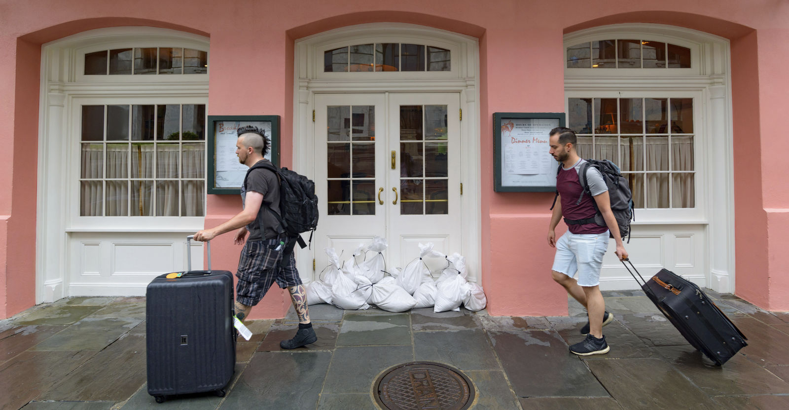 People walk past Brennan's restaurant in the French Quarter with sandbags on the front door as bands of rain from Tropical Storm Barry from the Gulf of Mexico move into New Orleans, La., Friday, July 12, 2019. (AP Photo/Matthew Hinton)