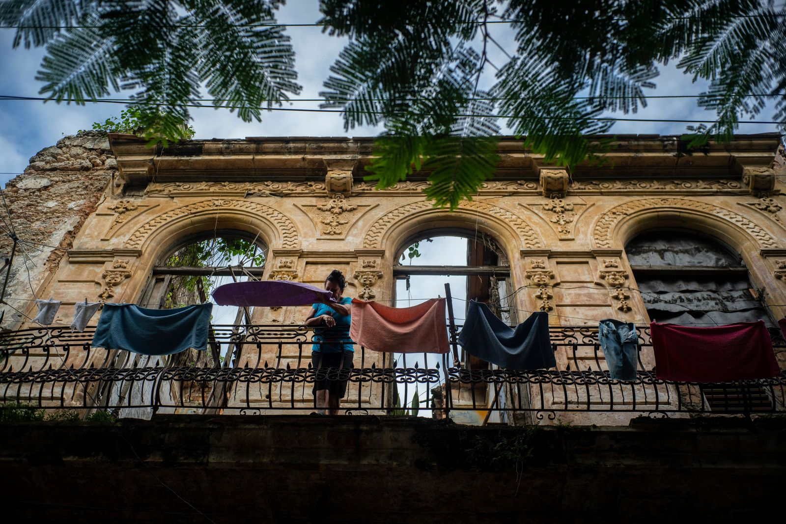 In this Nov. 10, 2019 photo, a woman pulls towels off the line after they dried on the balcony of an old home, missing part of its roof, in Havana, Cuba. The city will celebrate its 500th anniversary on Nov. 16. (AP Photo/Ramon Espinosa)