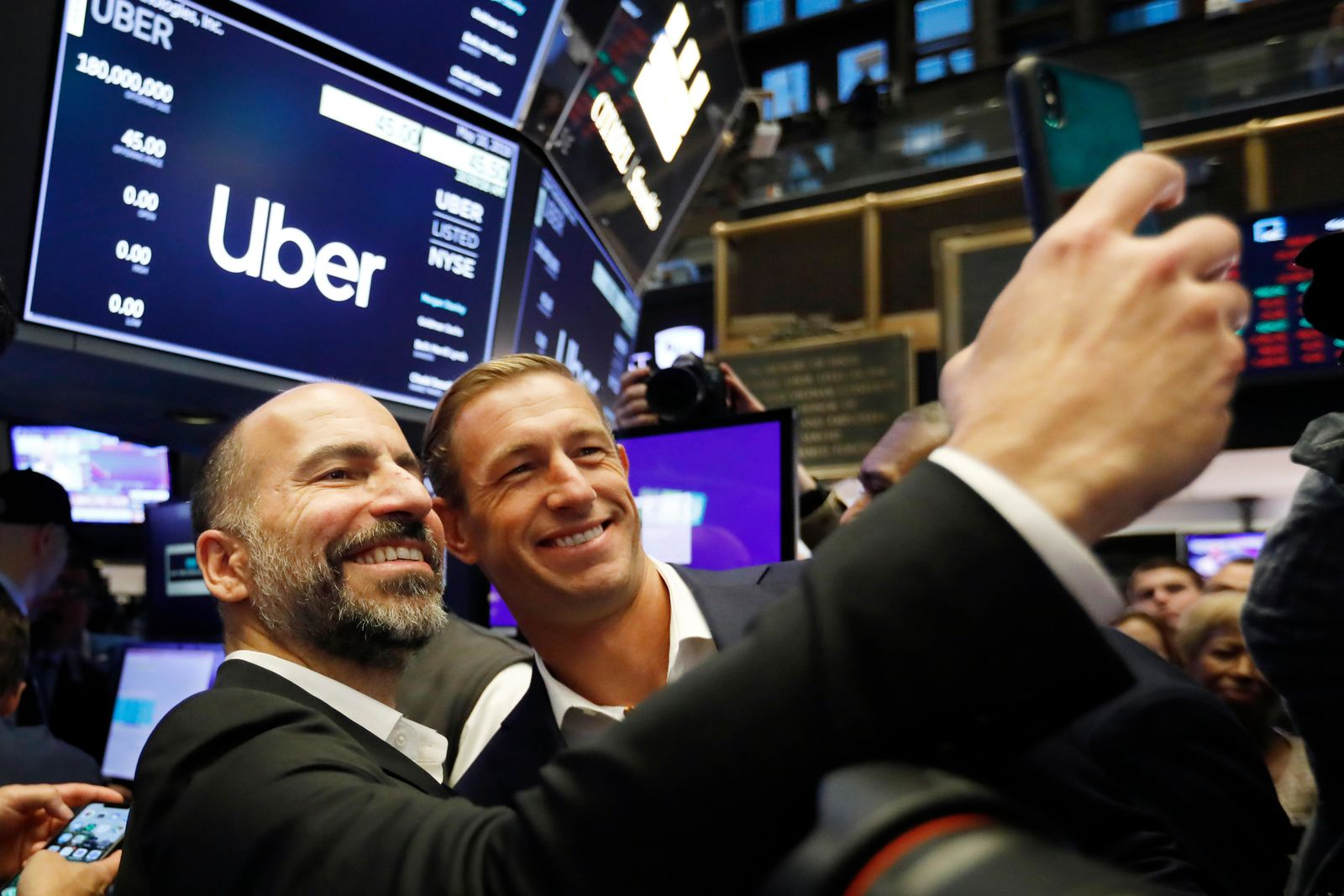 Uber CEO Dara Khosrowshahi, left, and Ryan Graves, a board member, pose for a photo before the company lists during its initial public offering at the New York Stock Exchange, Friday, May 10, 2019. (AP Photo/Richard Drew)
