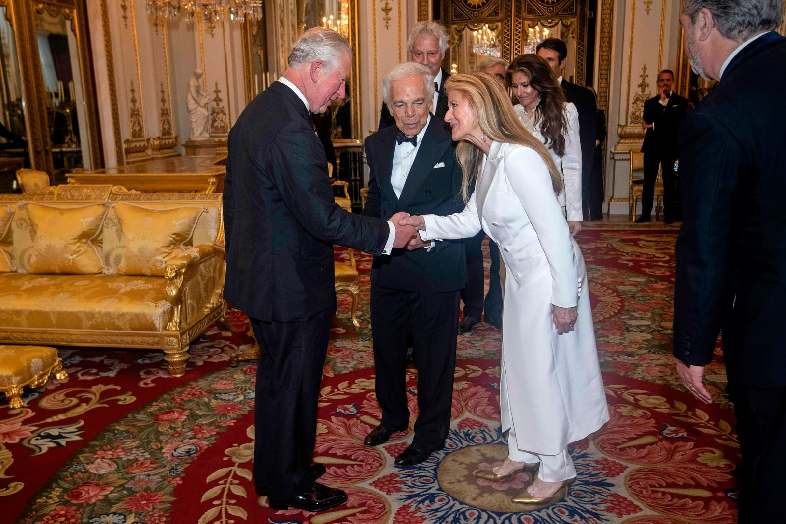 The Prince of Wales, designer Ralph Lauren, center, and his wife Ricky Lauren after he was presented with his honorary KBE (Knight Commander of the Order of the British Empire) for Services to Fashion in a private ceremony at Buckingham Palace Wednesday June 19, 2019.  (Victoria Jones/PA via AP)