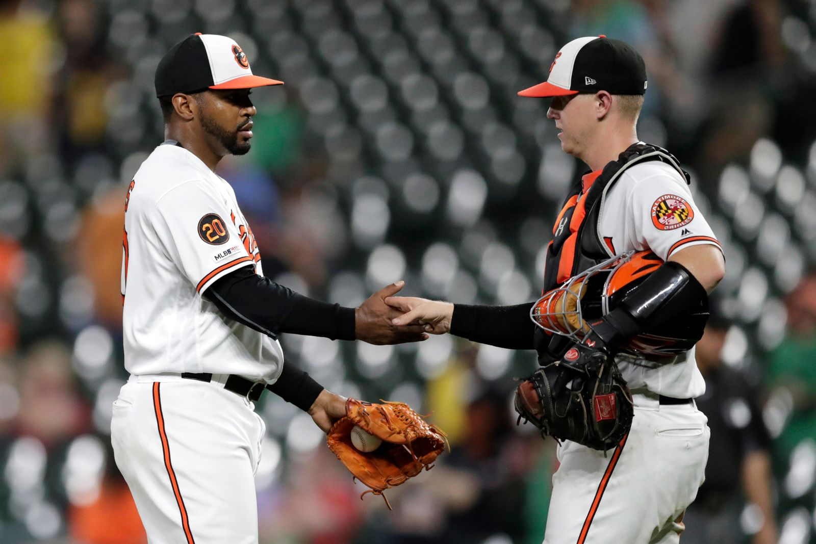 Baltimore Orioles relief pitcher Mychal Givens left, shakes hands with catcher Chance Sisco after the Orioles defeated the Washington Nationals 9-2 in a baseball game Wednesday, July 17, 2019, in Baltimore. (AP Photo/Julio Cortez)