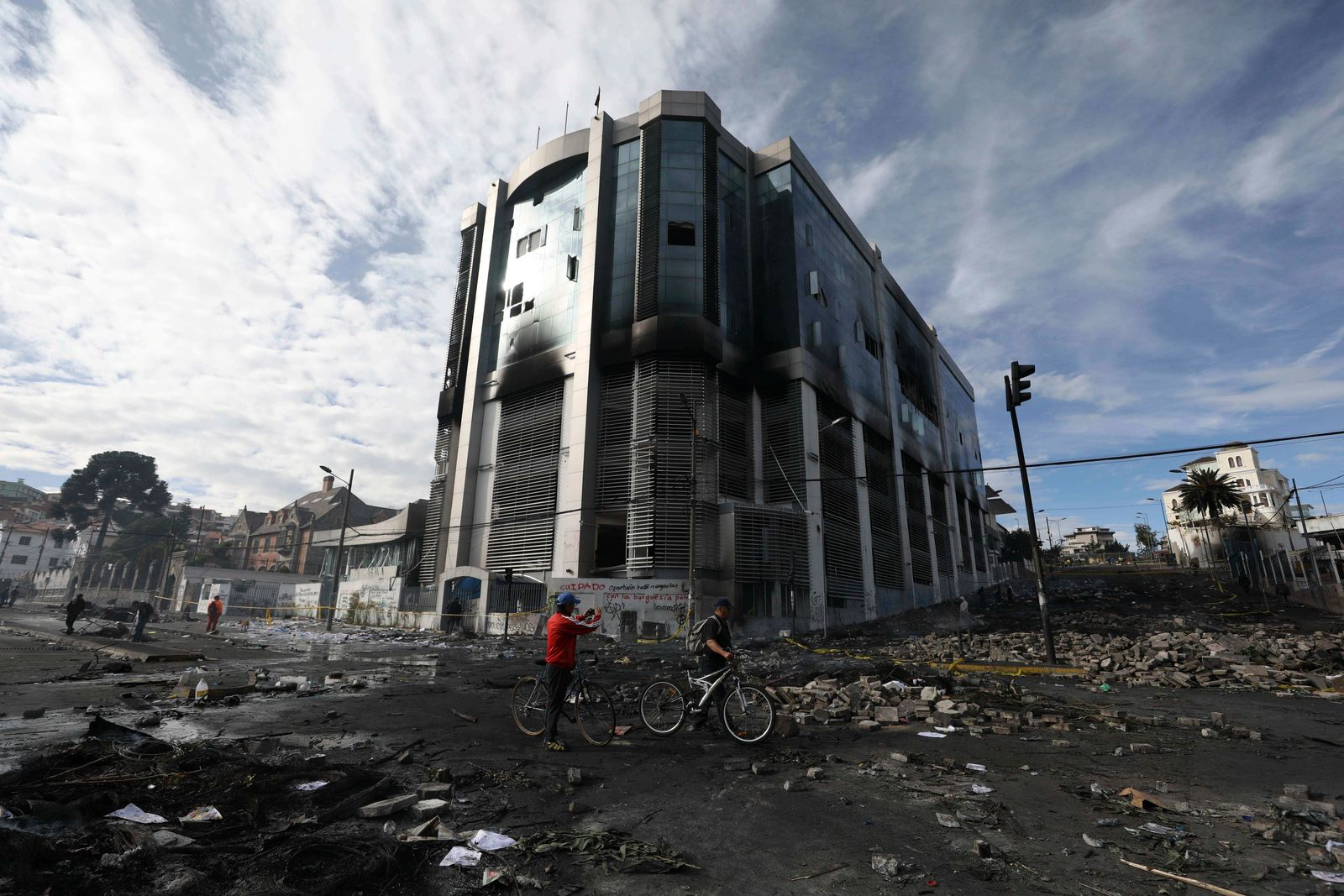 A cyclist takes a photograph of the national auditor's office the day after it was attacked by anti-government protesters in Quito, Ecuador, Sunday, Oct. 13, 2019.{ } (AP Photo/Fernando Vergara)