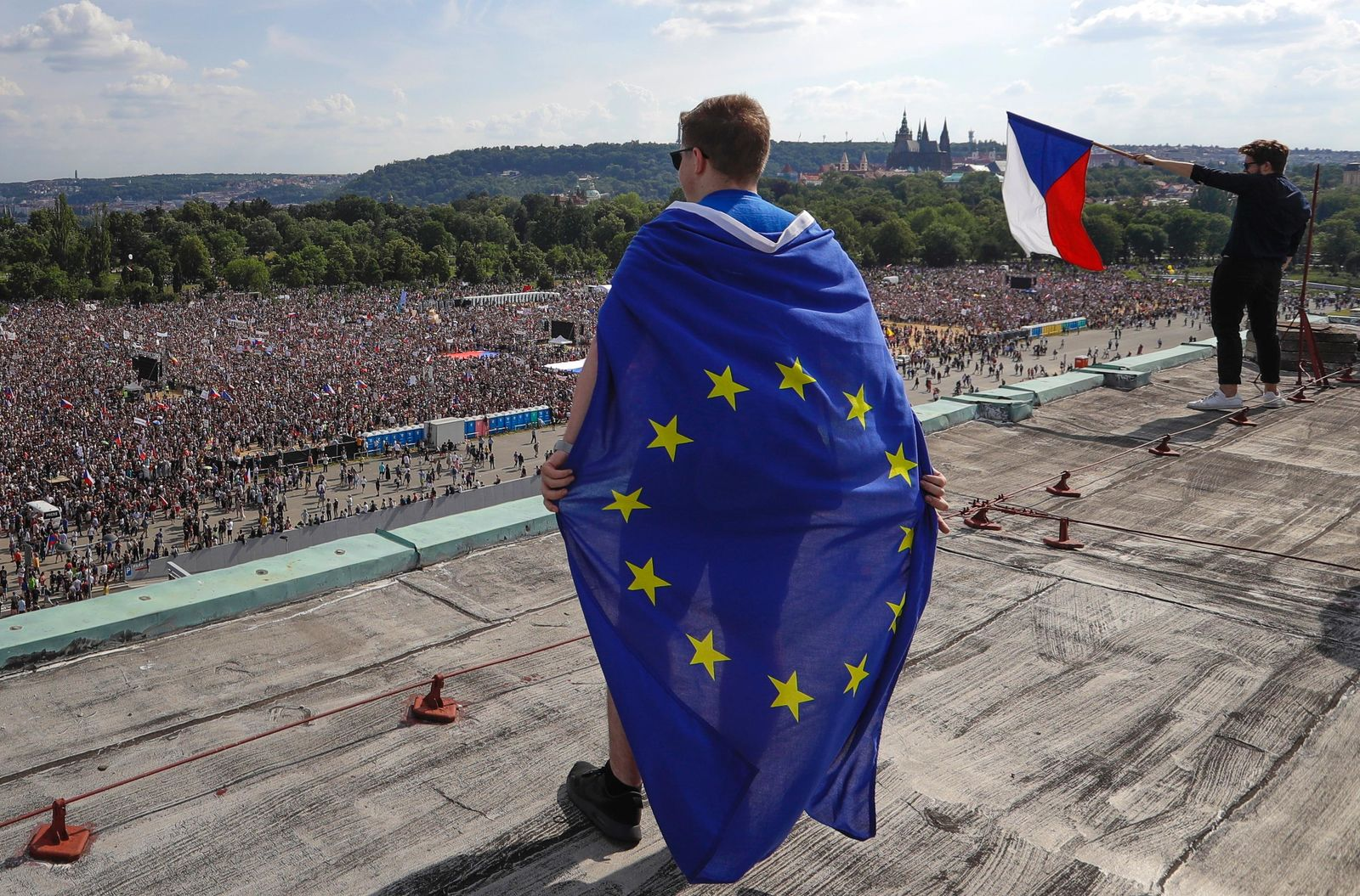 A man wrapped in a European Union flag watches protesters gather in Prague, Czech Republic, Sunday, June 23, 2019. Protesters are on calling on Czech Prime Minister Andrej Babis to step down over fraud allegations and subsidies paid to his former companies. (AP Photo/Petr David Josek)