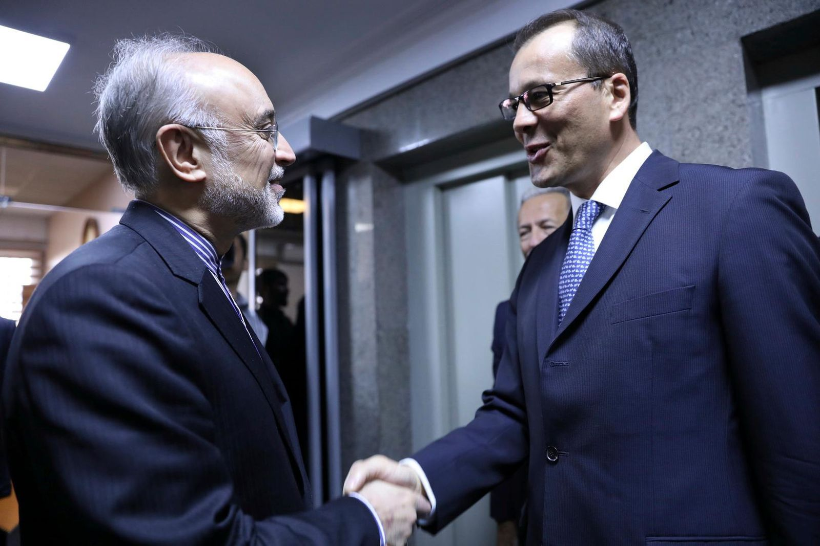 In this photo released by the Atomic Energy Organization of Iran, the head of Iran's nuclear program, Ali Akbar Salehi, left, shakes hands with acting chief of the International Atomic Energy Agency, IAEA, Cornel Feruta, during their meeting in Tehran, Iran, Sunday, Sept. 8, 2019. (Atomic Energy Organization of Iran via AP)