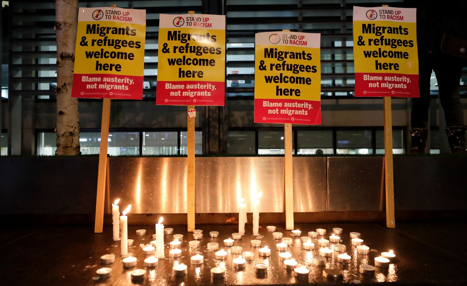Signs and candles on a wall were placed at a vigil for the 39 lorry victims, outside the Home Office in London, Thursday, Oct. 24, 2019.{ } (AP Photo/Kirsty Wigglesworth)