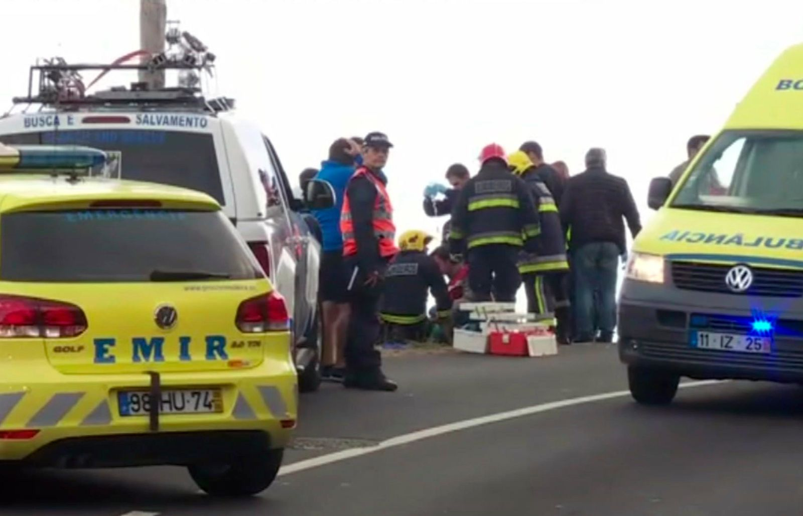 In this image from video, emergency services attend to injured at the scene after a tour bus crashed at Canico, on Portugal's Madeira Island, Wednesday April 17, 2019.  Some 28 people are reported to have died in the crash, most of them German tourists, local mayor Filipe Sousa told TV news. (TVI via AP)