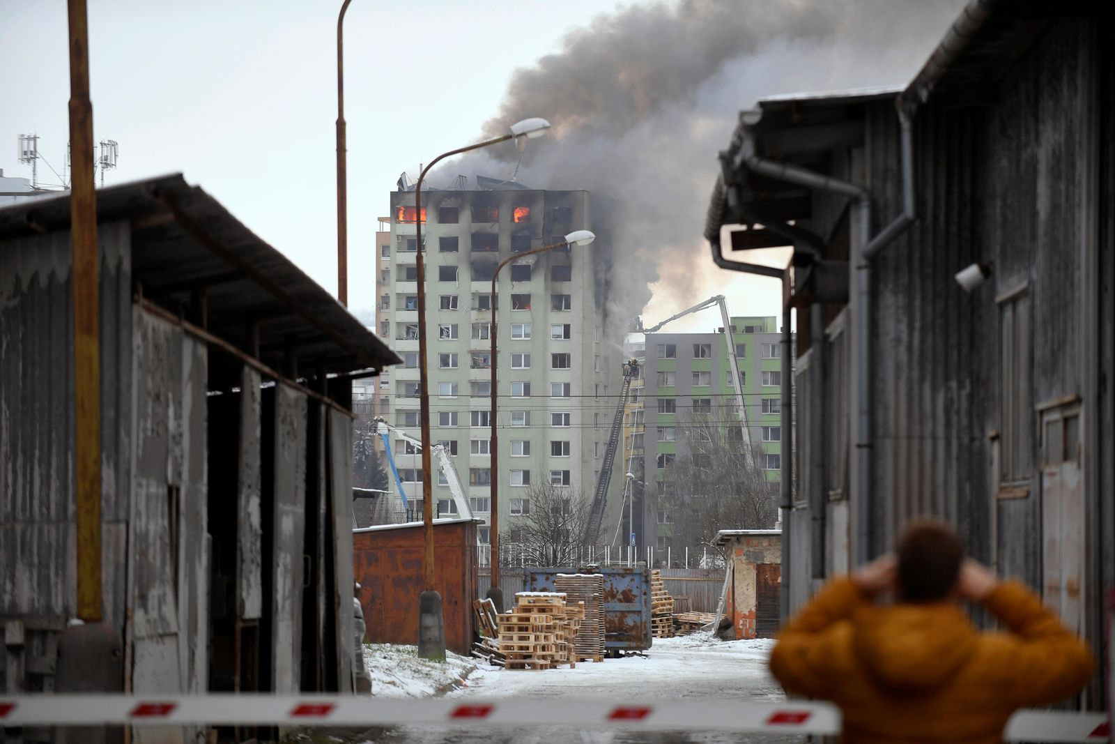 Smoke rise from a damaged 12-storey apartment block after a gas explosion in Presov, Slovakia, Friday, Dec. 6, 2019. Officials say a gas explosion in an apartment block in Slovakia has killed at least five people and others are trapped on the roof of the building. Firefighters say the explosion occurred in a 12-story building in the city of Presov shortly after noon on Friday.  (Frantisek Ivan/TASR via AP)