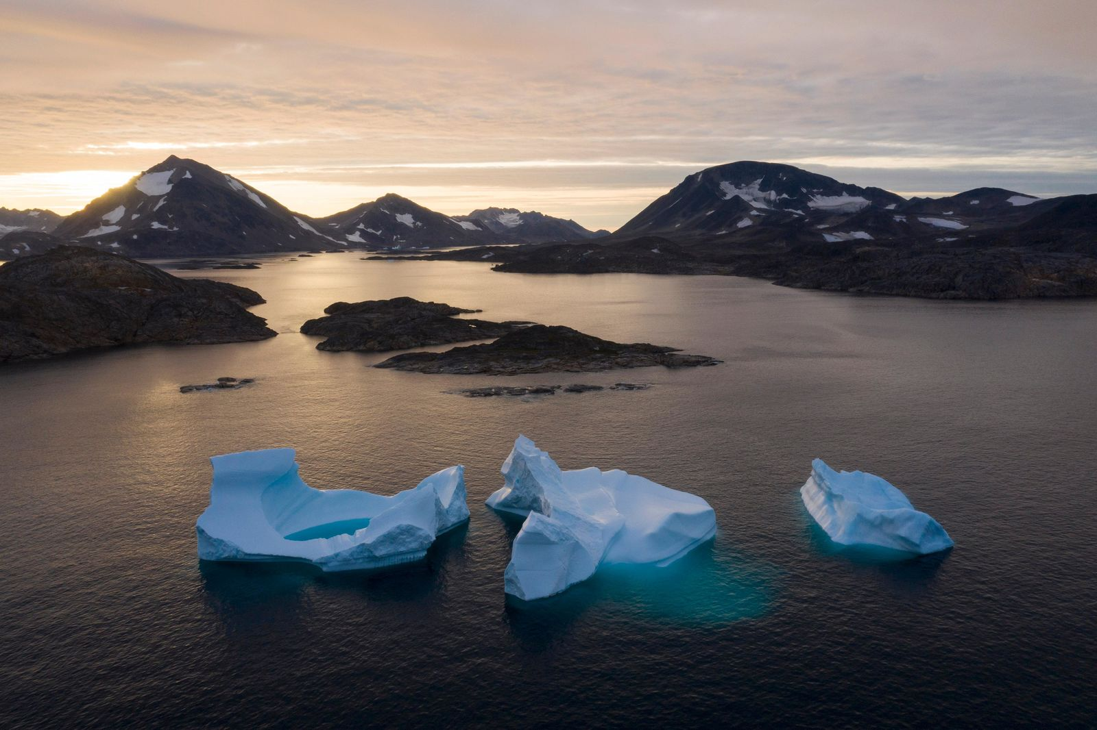 In this Aug. 16, 2019, photo, large Icebergs float away as the sun rises near Kulusuk, Greenland. (AP Photo/Felipe Dana)