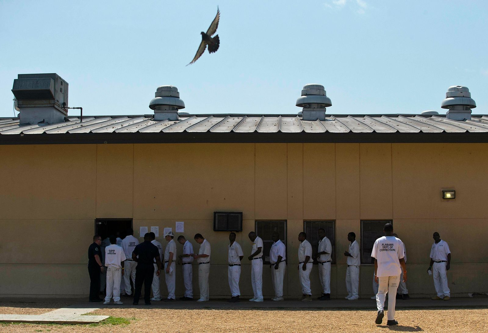 FILE - In this June 18, 2015, file photo, prisoners stand in a crowded lunch line during a prison tour at Elmore Correctional Facility in Elmore, Ala. (AP Photo/Brynn Anderson, File)
