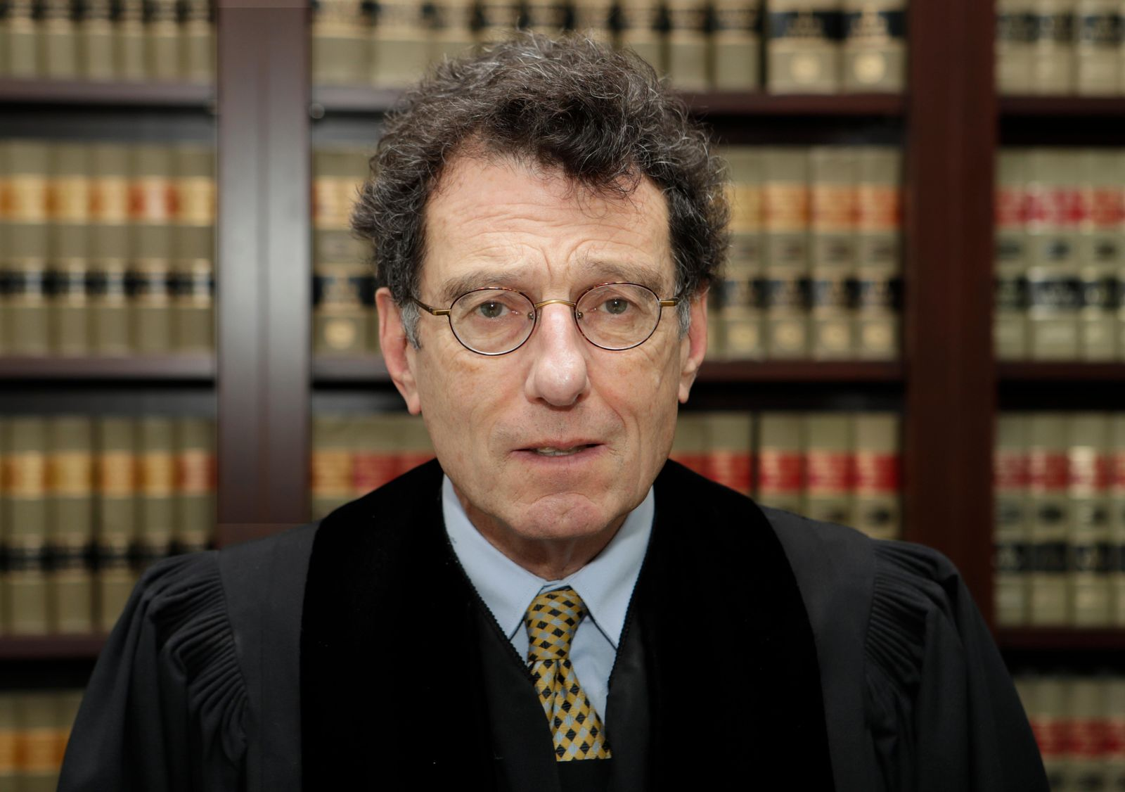 FILE - This Jan. 11, 2018 file photo shows Judge Dan Polster in his office, in Cleveland.  Attorneys representing eight drug distributors, pharmacies and retailers facing trial for their roles in the national opioid crisis are seeking to disqualify the federal judge overseeing their cases saying he's shown clear bias in his efforts to obtain a multi-billion dollar global settlement. The motion was filed late Friday, Sept. 13, 2019,  in U.S. District Court in Cleveland, where Judge Dan Polster presides over most of the 2,000 lawsuits filed by state, local and tribal governments. Polster has not responded.  (AP Photo/Tony Dejak, File)